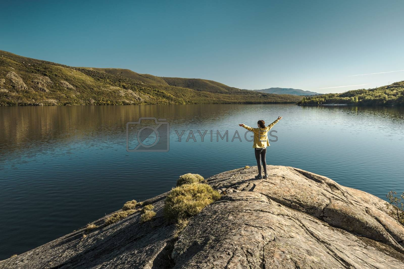 Shot of a woman hiking near a beautiful lake with arsm raised