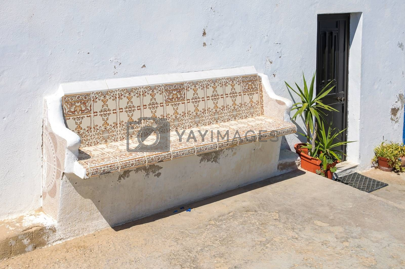 Bench decorated with traditional portuguese tiles called azulejos ath the house entrance