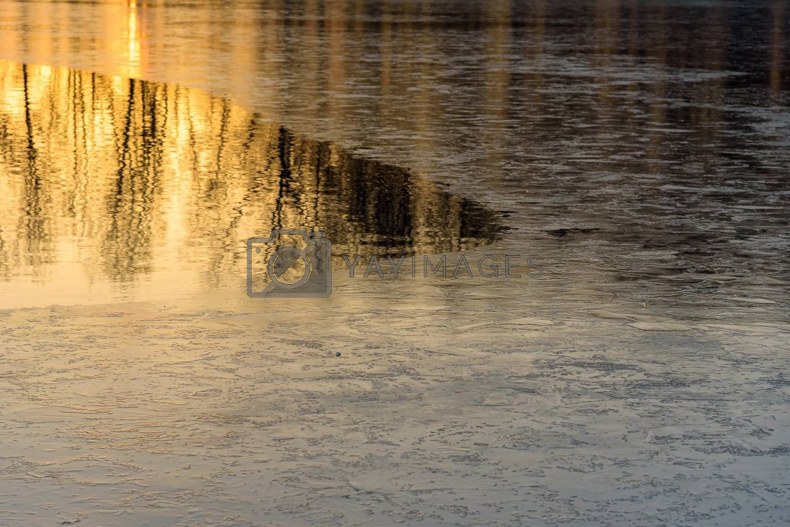 Natural winter background made of half frozen lake at sunset