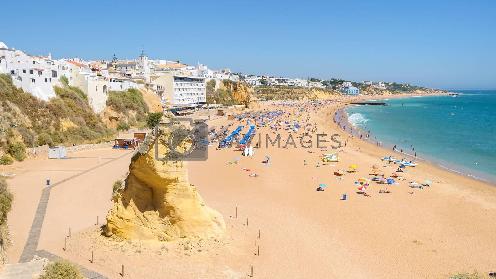 View of sunny public beach with sandstone rock in Albufeira, Algarve, Portugal