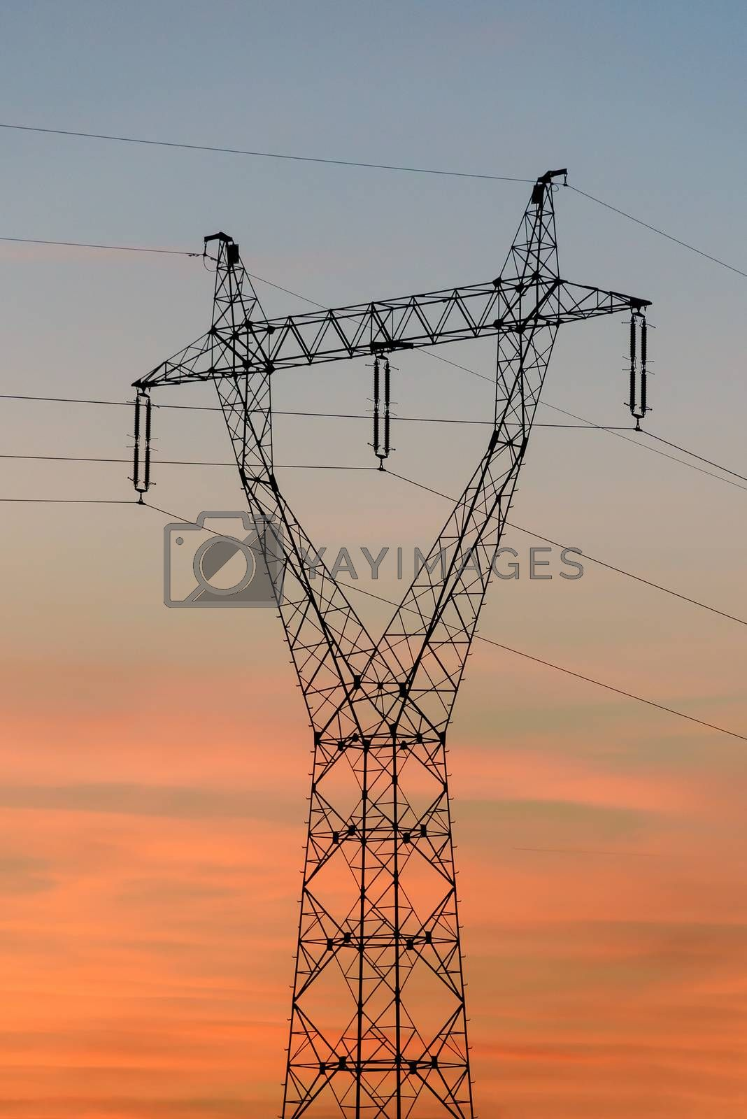 Closeup of electricity pylon and high voltage power lines at sunset