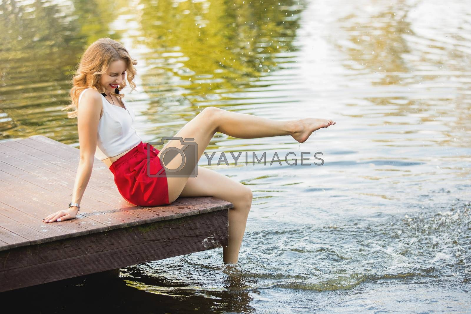 happy attractive young woman at a lake having fun and splashing water sitting on the pier in summer. good time.