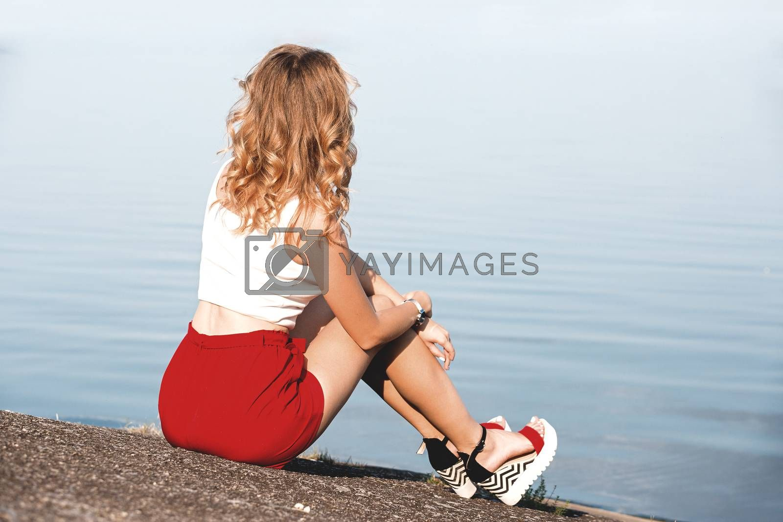 Back view of lonely caucasian girl sitting on the ground near lake at morning time
