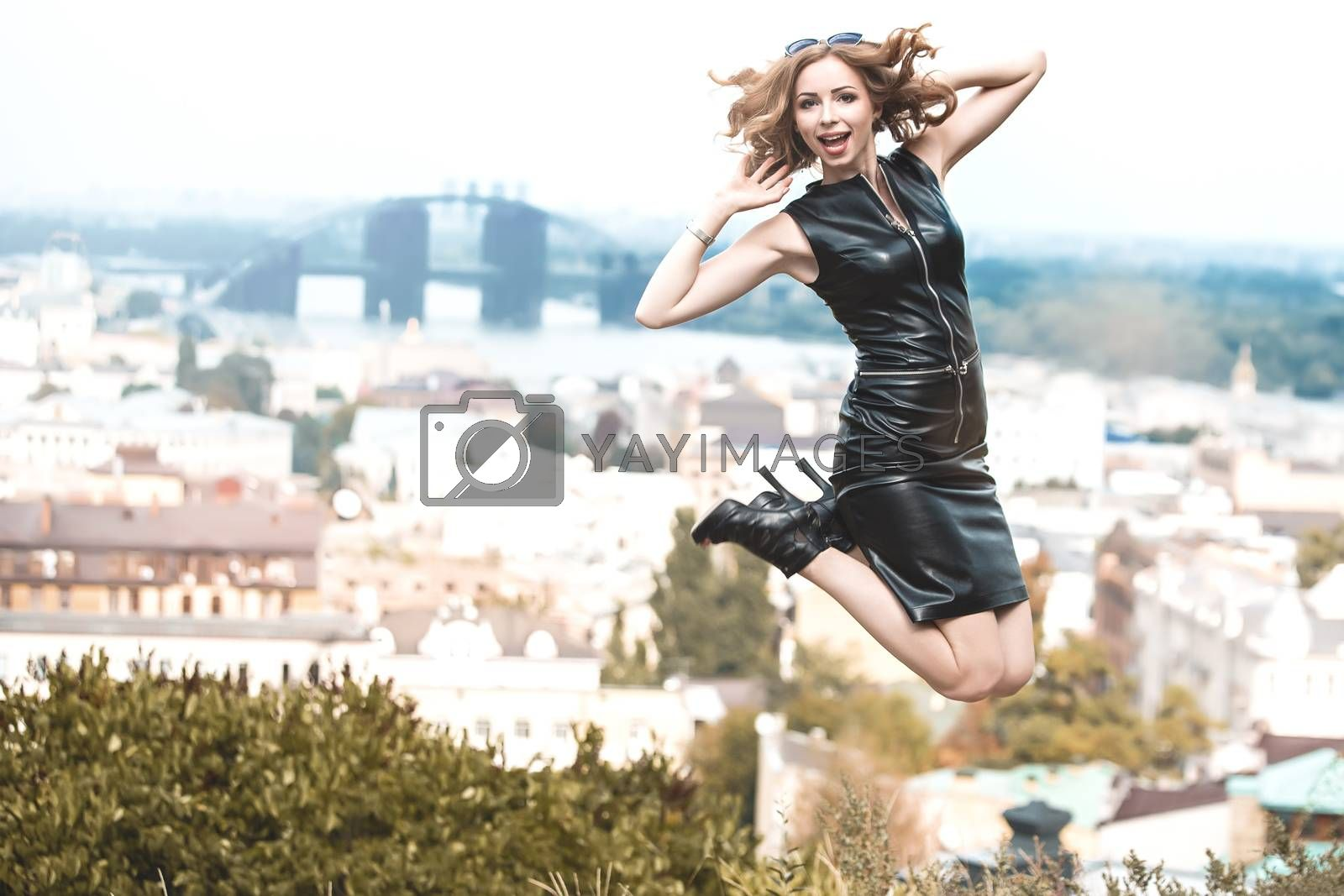 Expressive girl with long hair having fun in city park. She wears in black skin dress. She is jumping excited.