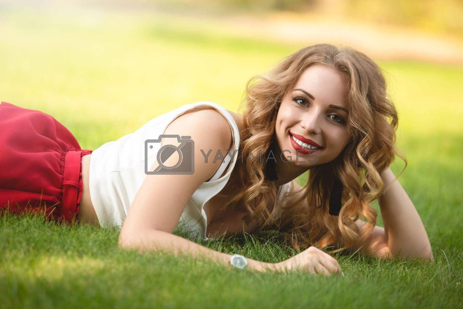 Top view of attractive female model lying on green grass in park and looking at camera during time for taking rest, portrait of Caucasian woman with blond hair spending day at nature.summer time