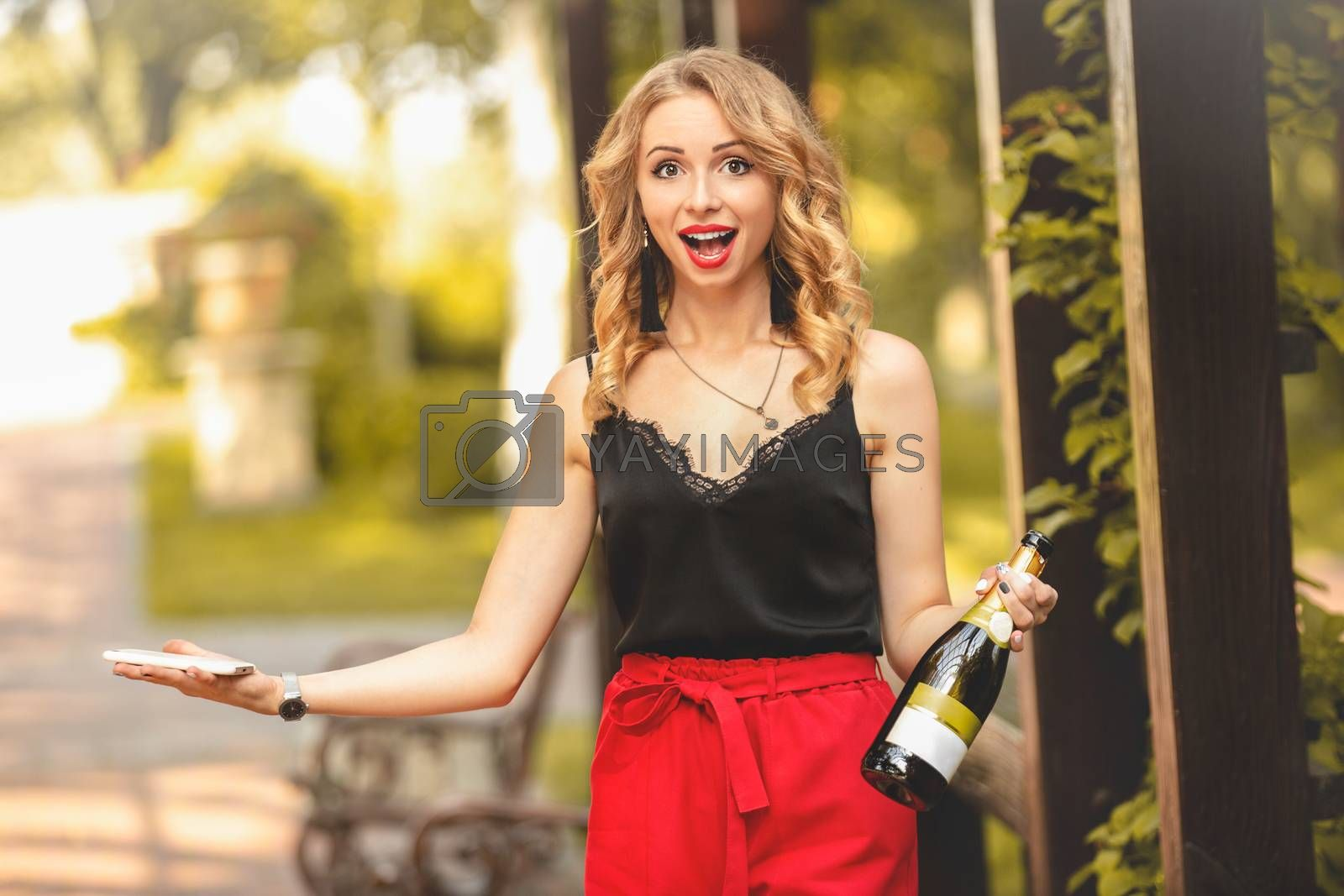 Happy young attractive white woman laughing joyfully, talking on the phone, holding a bottle of champagne and calling for a party. emotions lifestyle leisure relaxation positive communication.