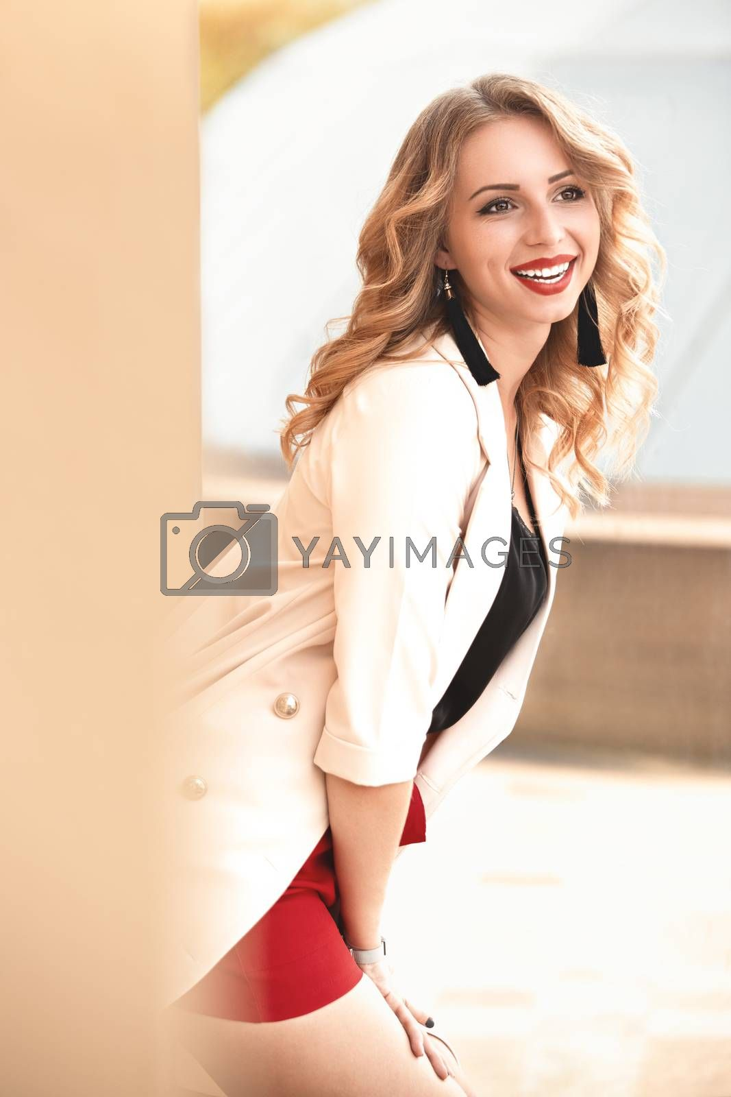 Beautiful young girl standing near the stone wall. Portrait pretty young fashion girl near a stone wall. Beautiful blonde woman with long hair posing near a stone wall.