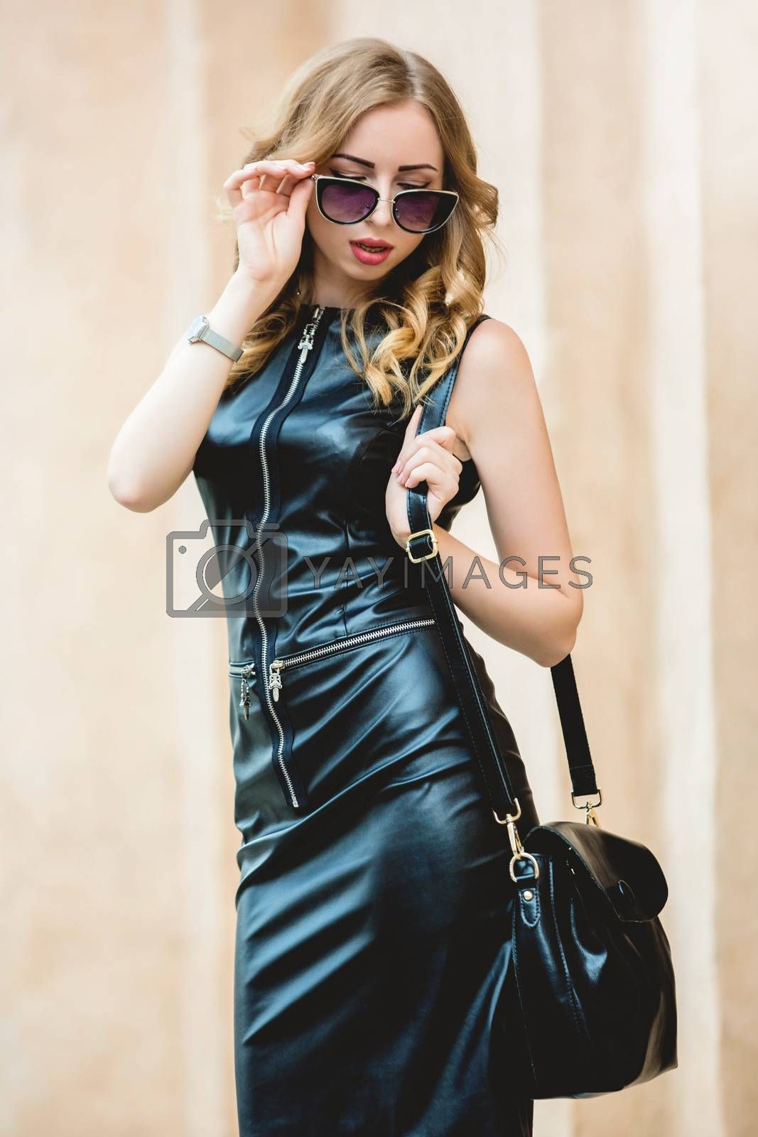 glamorous woman with glasses dressed in a black stylish dress after shopping. shopping time concept.