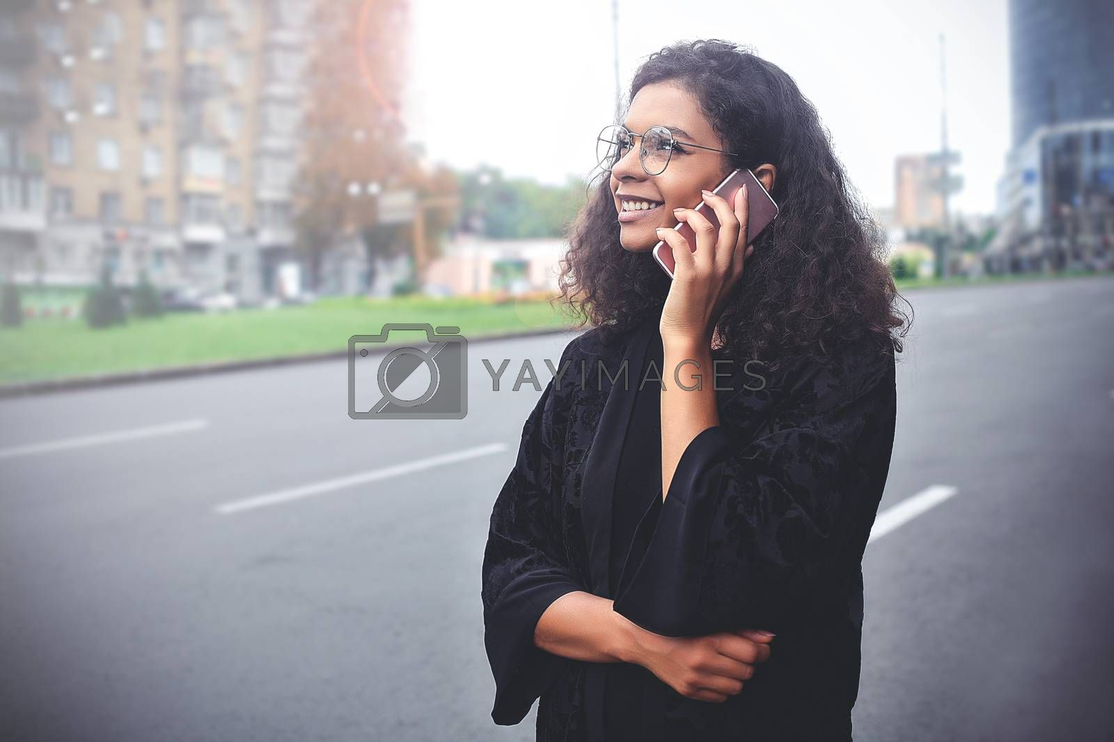 Positive emotions. Lifestyle concept. Close up of young mixed race woman use a phone.