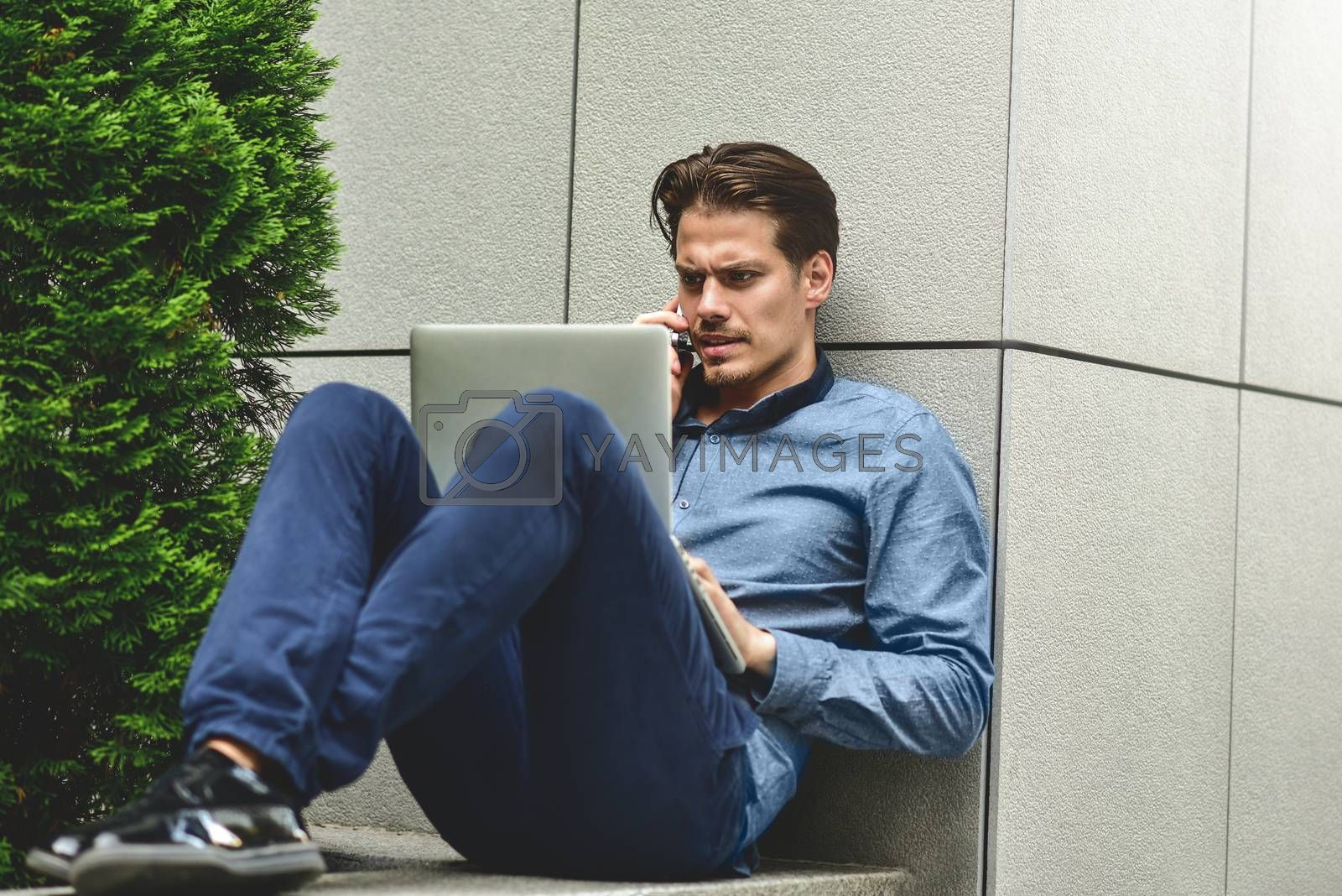 Young attractive guy who is smiling looking at his laptop screen during video call. Young man using laptop.