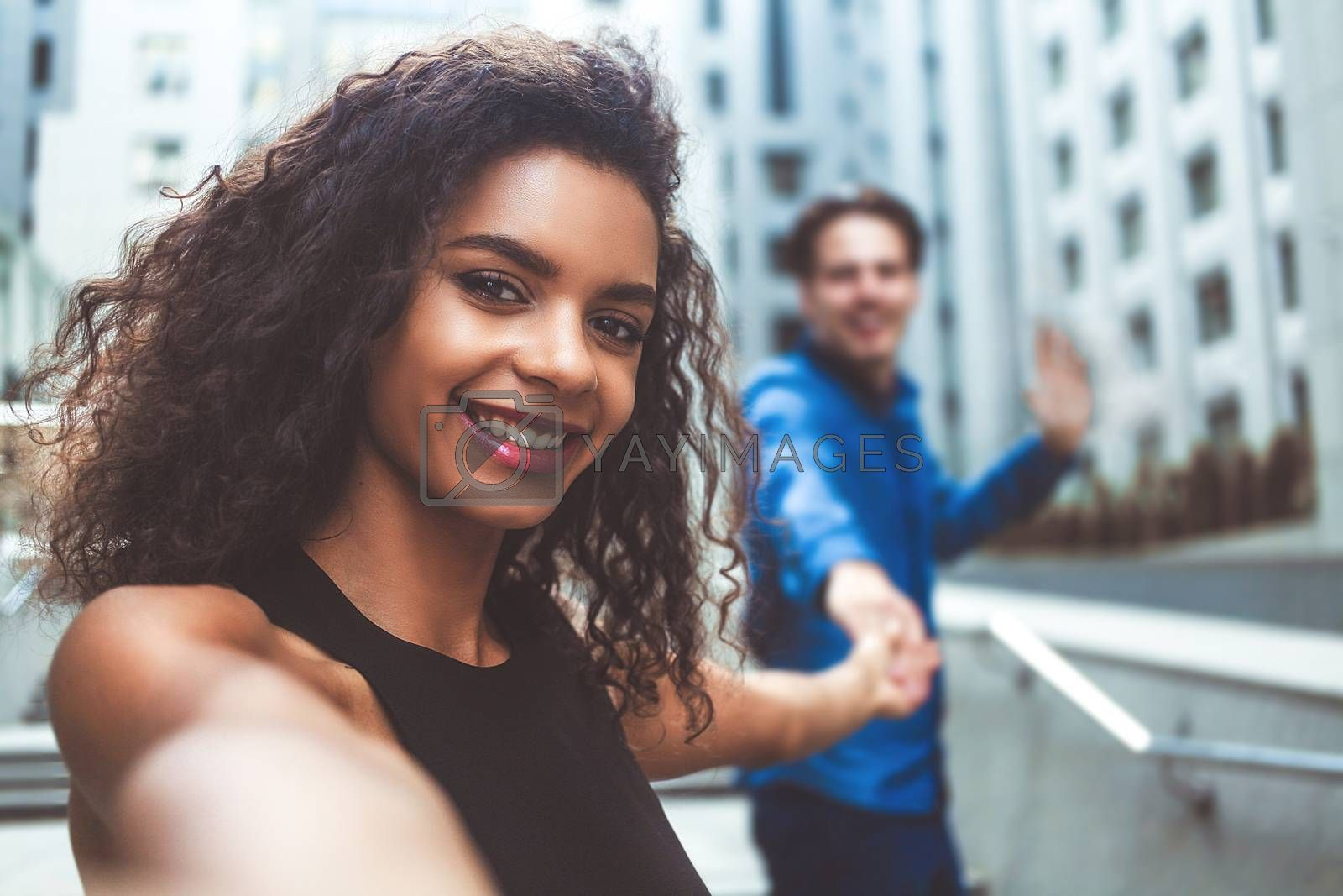Outdoor portrait beautiful happy afroamerican woman taking selfie photograph smiling laughing with perfect teeth at street.
