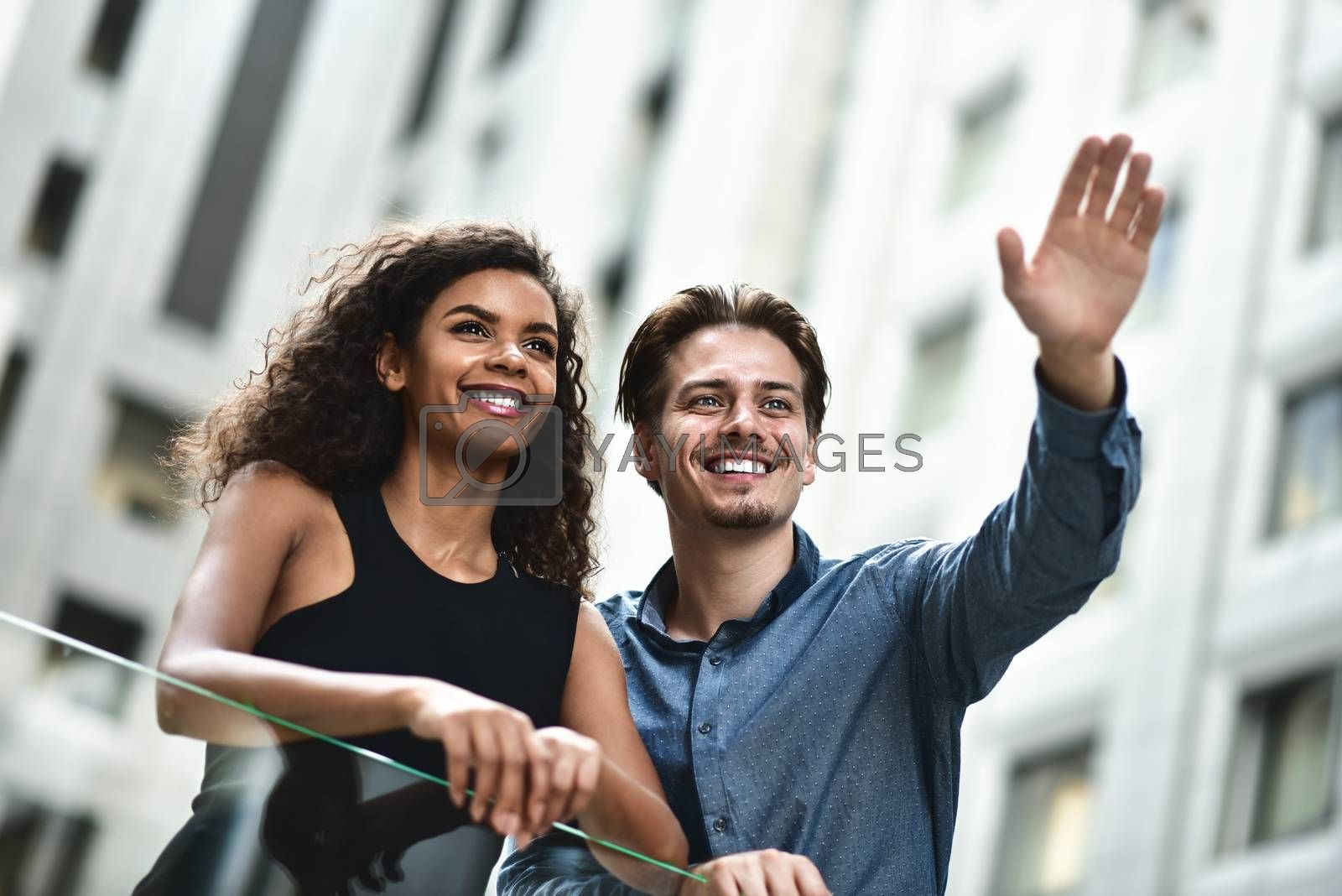 Happy international couple have a conversation in city. Mixed race woman and caucasian man.