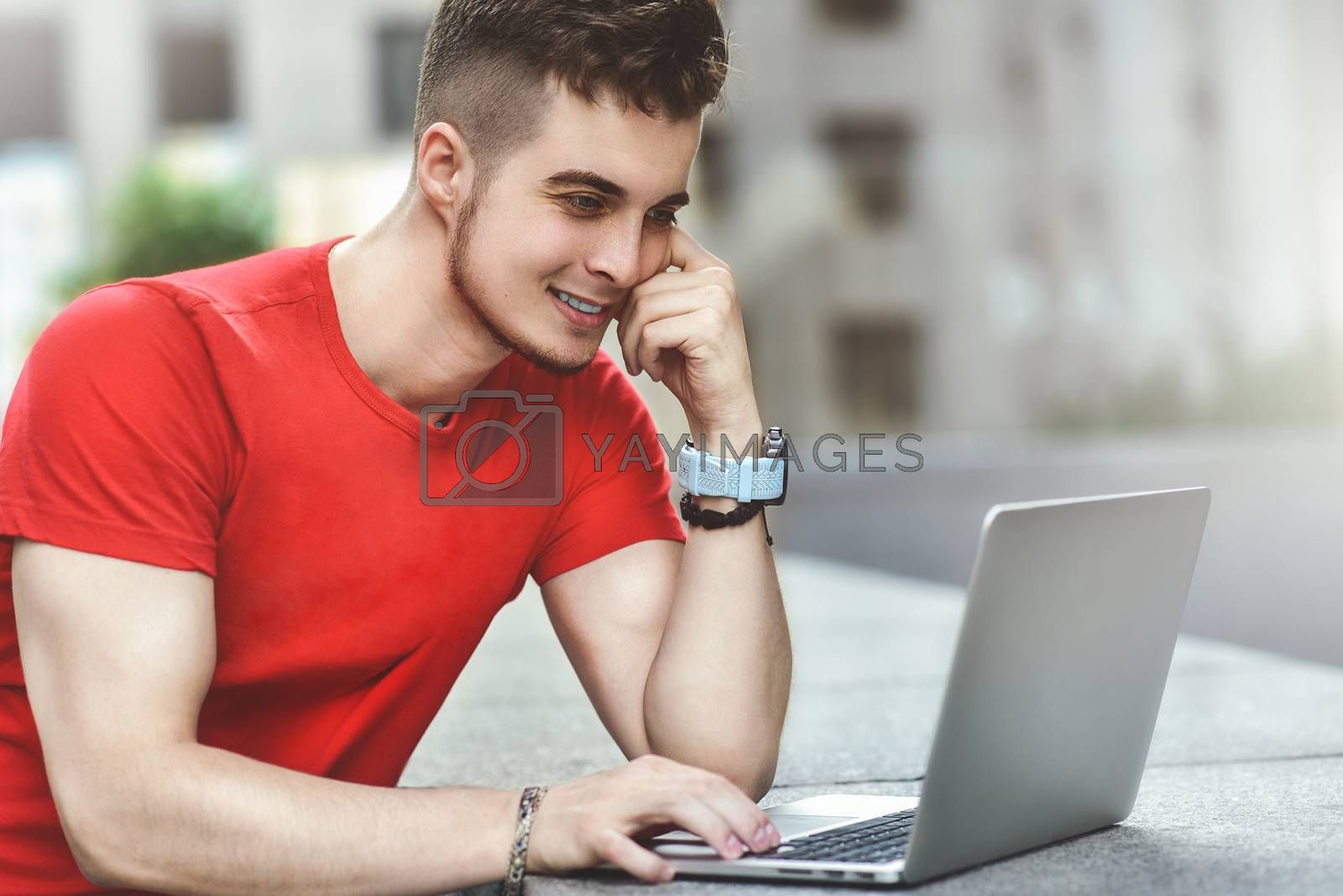 Young attractive guy who is smiling looking at his laptop screen . Young man using laptop.