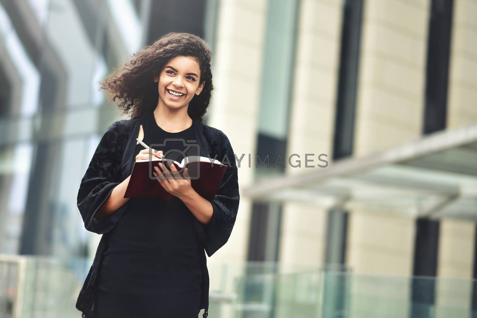 Charming Afro American beautiful happy female, making notes in notepad while walking outdoors on a city street. Education and business concept with space for text.