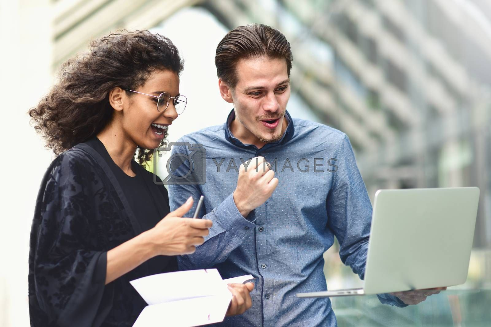 Business man and woman working on laptop together on building background in city outdoor feeling happy.