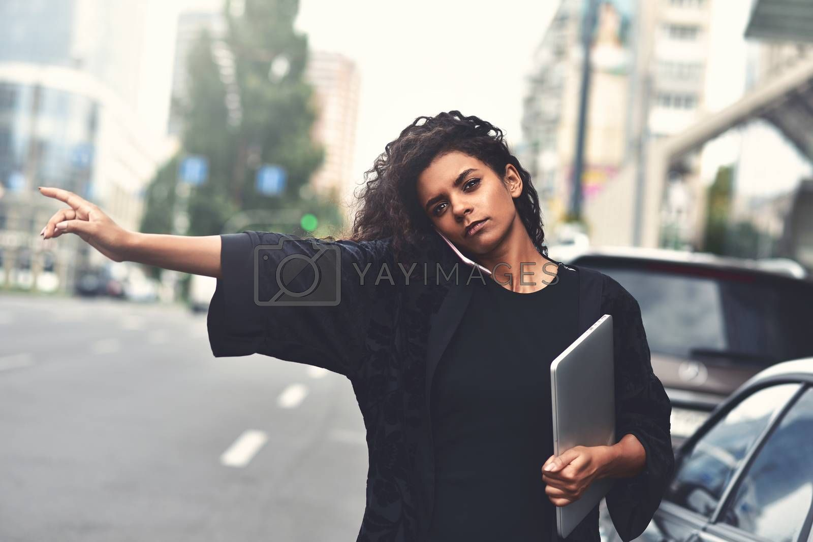 Young black girl try to take a taxi on the street holding a laptop
