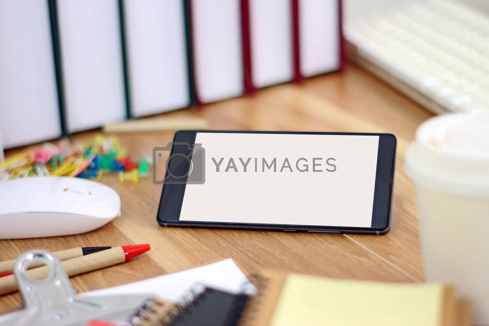 Workspace with smartphone and office equipments on wood desk work background