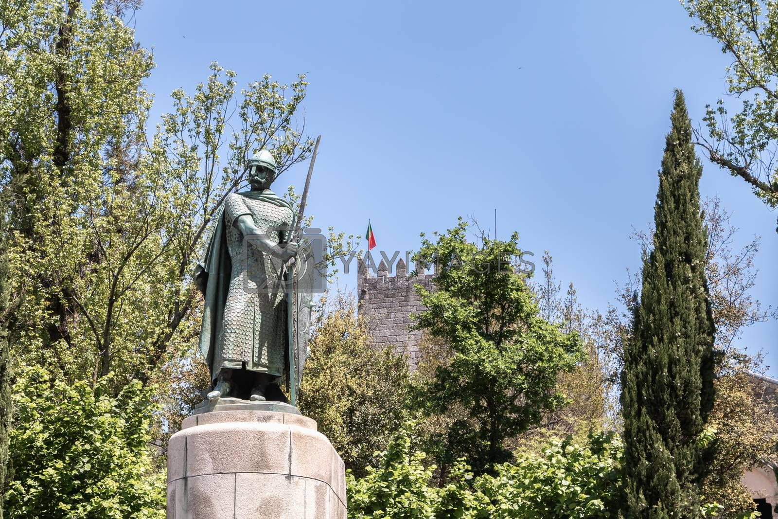 Guimaraes, Portugal - May 10, 2018: statue of the first king of Portugal, D. Afonso Henriques by the sculptor Antonio Soares dos Reis in front of the castle of Guimaraes that tourists are visiting on a spring day
