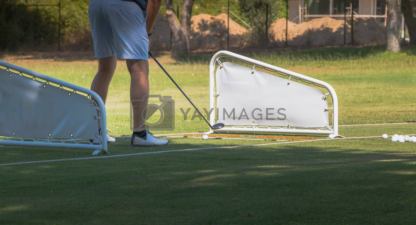 golf player making a swing with a golf  fairway wood course on the golf practice