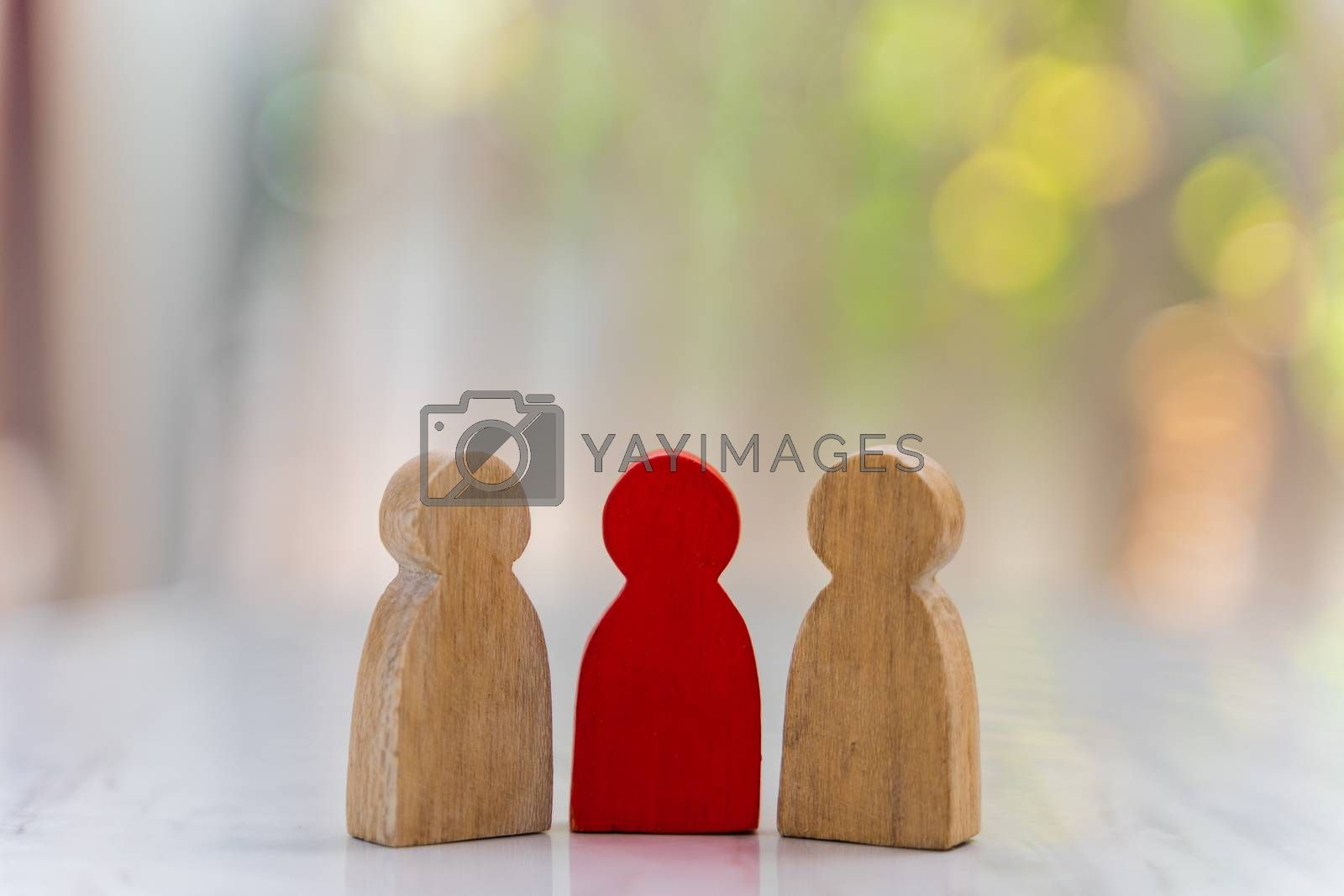 Figure in human resource management concept. The group of wooden puppets A red wooden figure like an dominant in a group with blur bokeh background