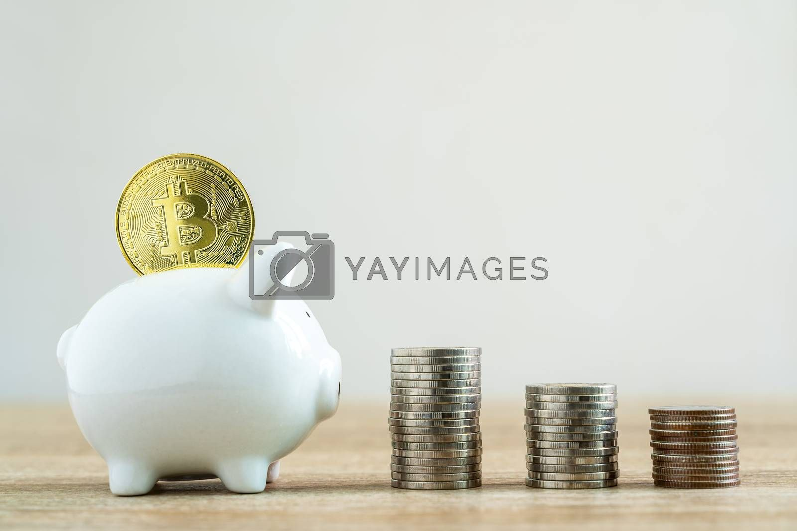 Money savings concepts stack coin with bitcoin to put in piggy bank to spend on expenses such as savings, tourism, investment, emergency, retirement on wooden table with blur background and copy space