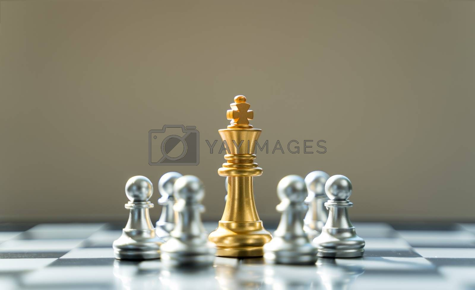 Golden King Chess is surrounded by silver chess, in conceptbusiness, triumph, success and competition. On board chess with a selective space copy focus at Golden King Chess