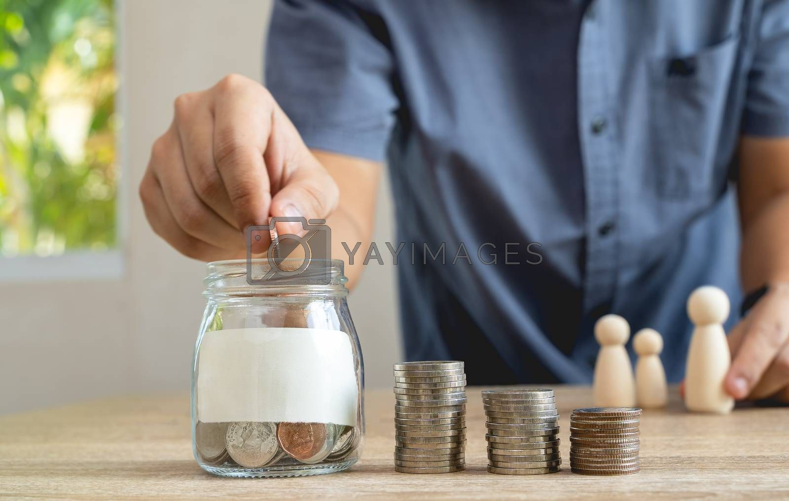Money savings concepts  Glass bottle and stack coins with blur Men are coining in Glass bottel for saving money for families with family wooden dolls on wooden table with blur background, selective focus