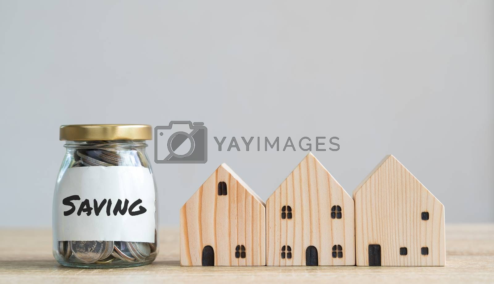 Money savings concepts. Wooden house models with coins in bottle and saving label meaning about saving money to buy a house, refinancing, investment or financial on wooden table with copy space
