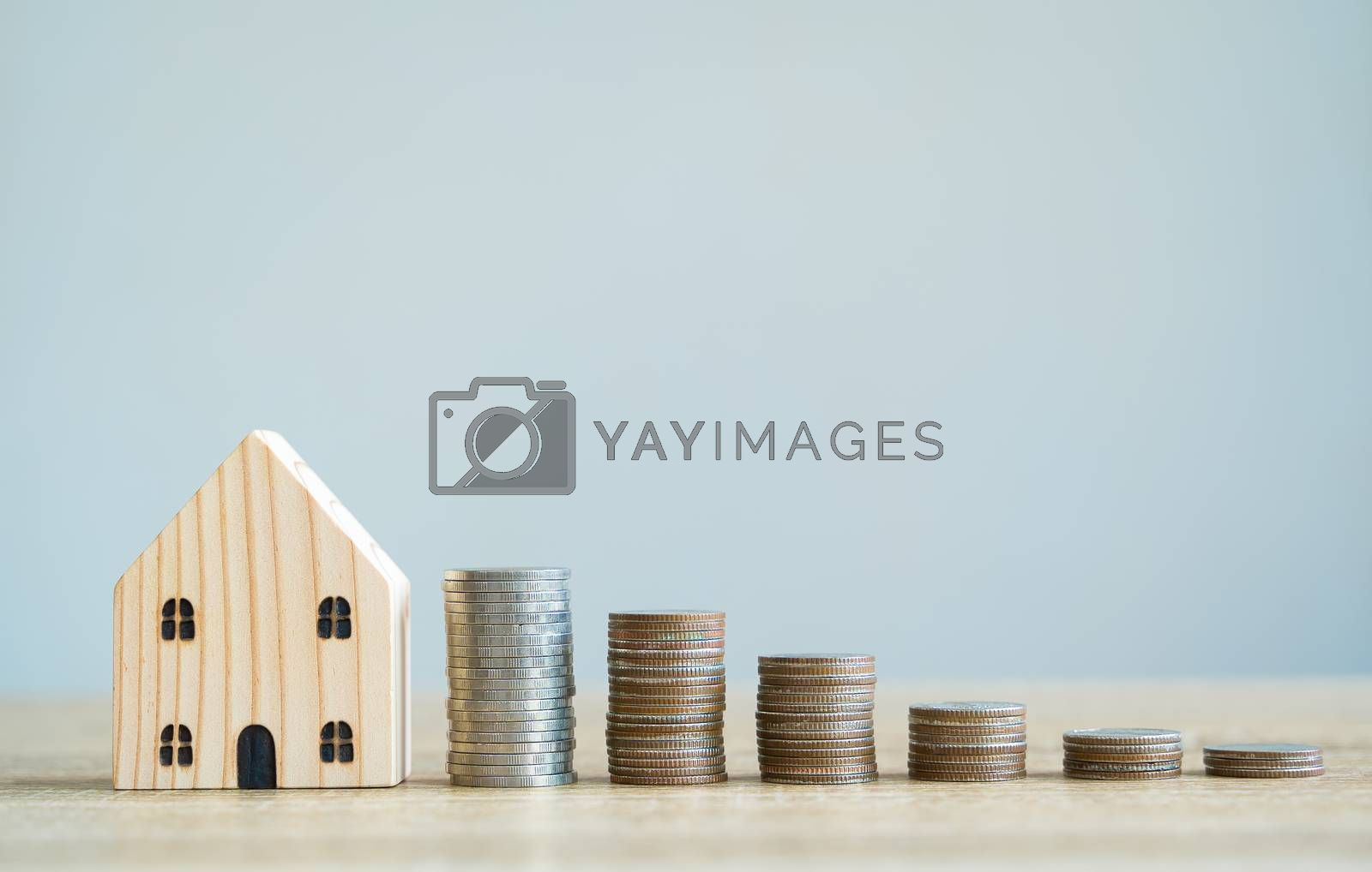 Money savings concepts. Wooden house models with stacked coins in meaning about saving money to buy a house, refinancing, investment or financial on wooden table with blur background and copy space