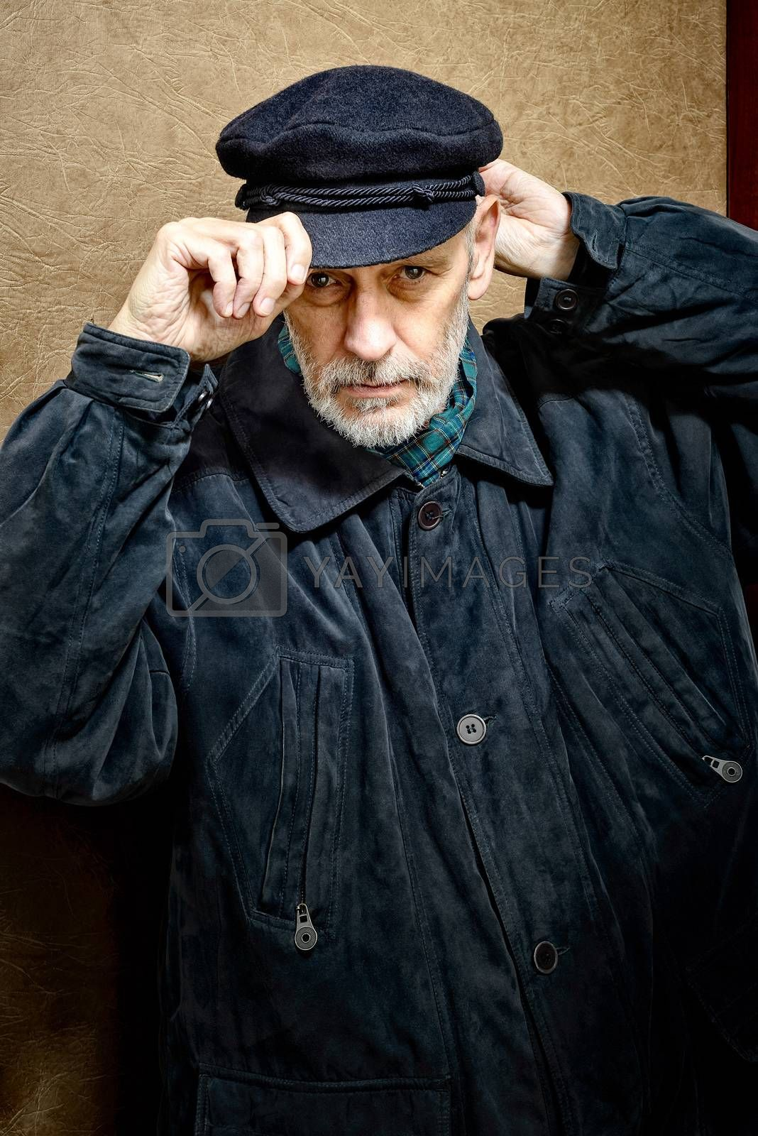 Portrait of a mature man with a white beard adjusting his cap on the head. He could be a sailor, a worker, a docker, or even a gangster or a thug. He has a penetrating gaze.