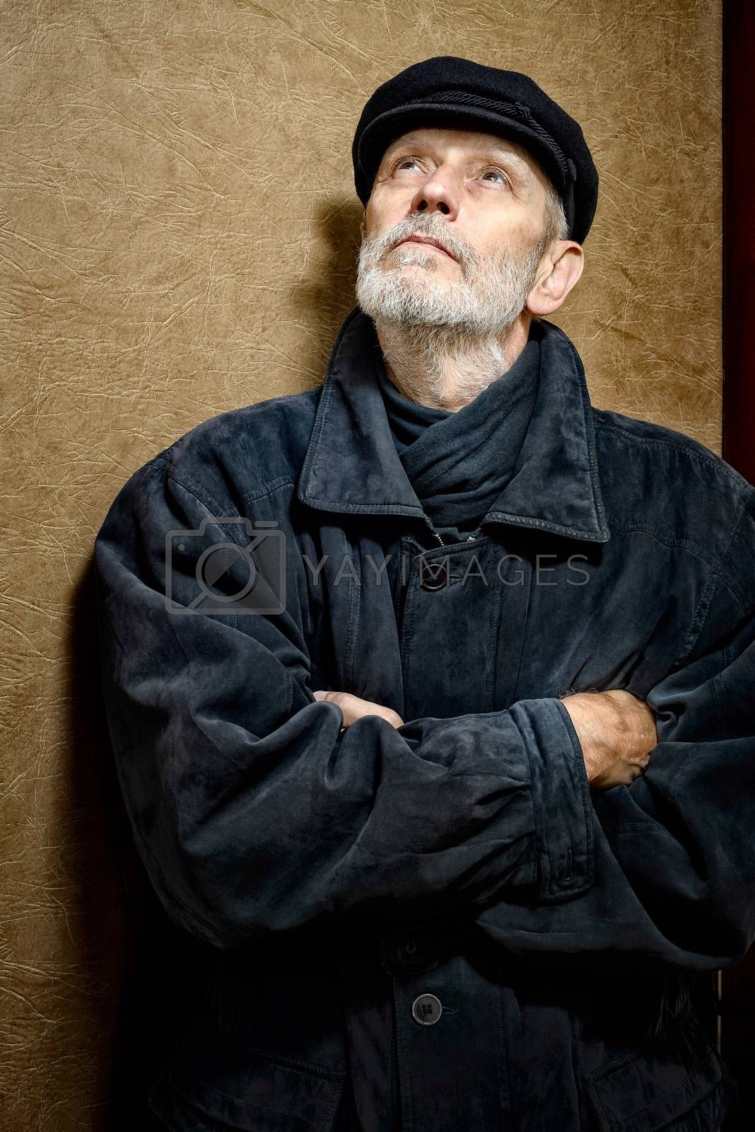 Portrait of a mature man with a white beard and a cap on the head. He could be a sailor, a worker, a docker, or even a gangster or a thug. He is looking up.