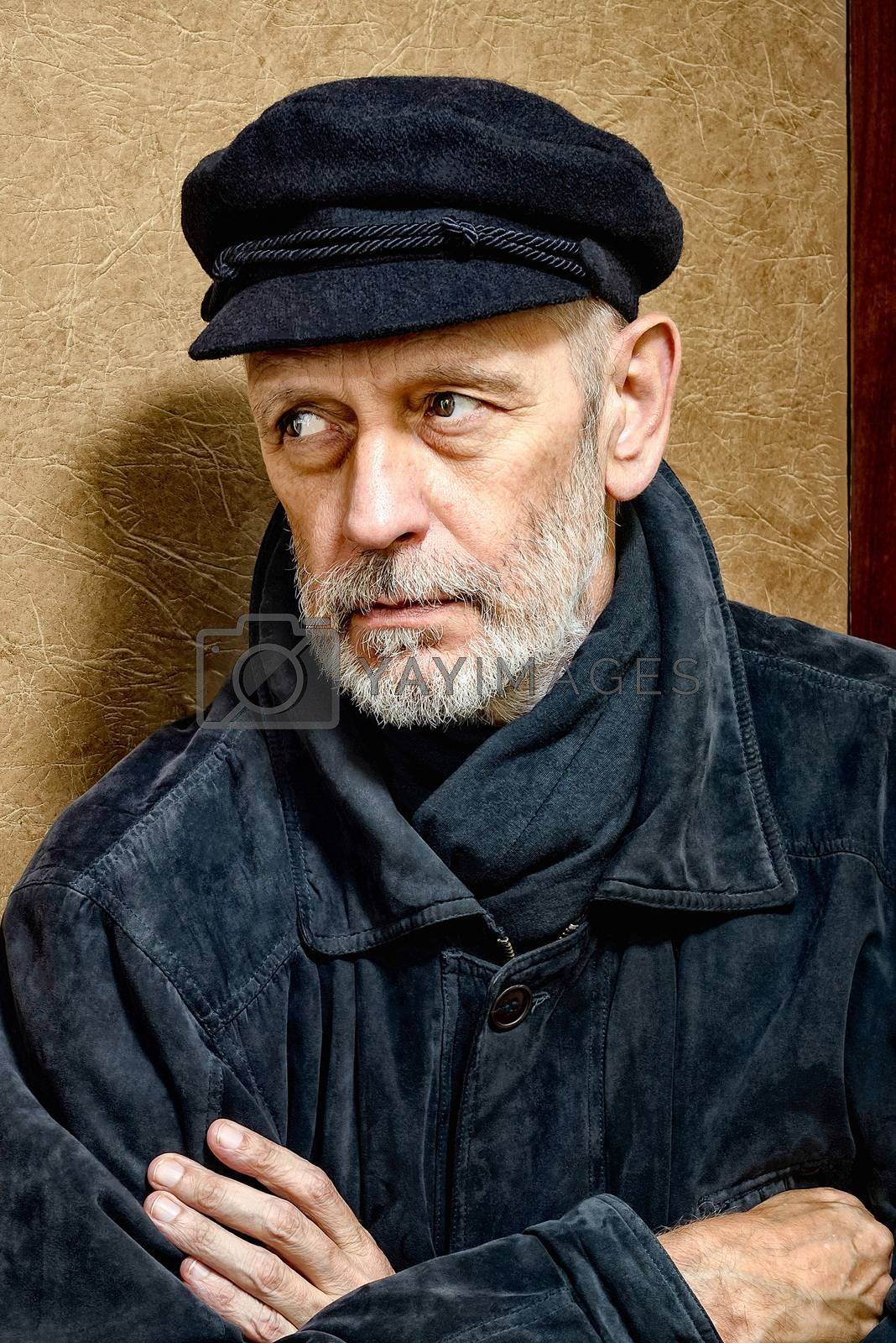 Portrait of a mature man with a white beard and a cap on the head. He could be a sailor, a worker, a docker, or even a gangster or a thug. He has a penetrating gaze.