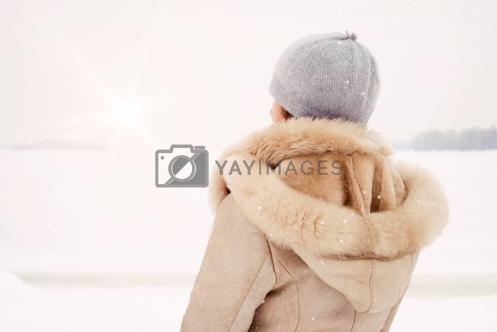 A woman with a wool cap and a leather coat is looking at the Dnieper river during a cold and magic winter morning under the snow