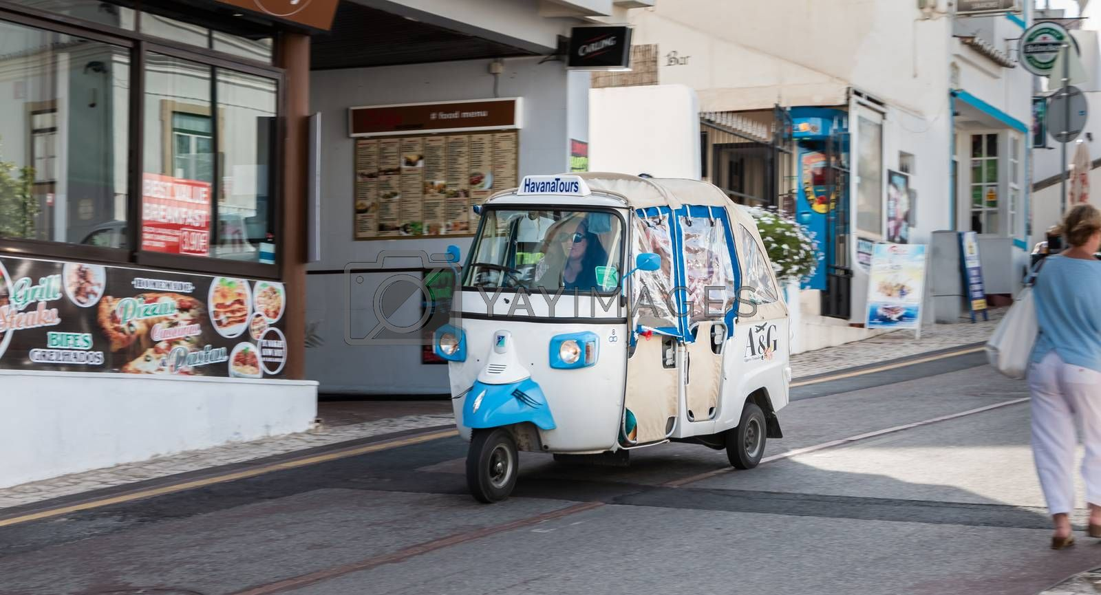 Albufeira, Portugal - May 3, 2018: Tuk Tuk carrying tourists traveling on a street in the historic city center on a spring day