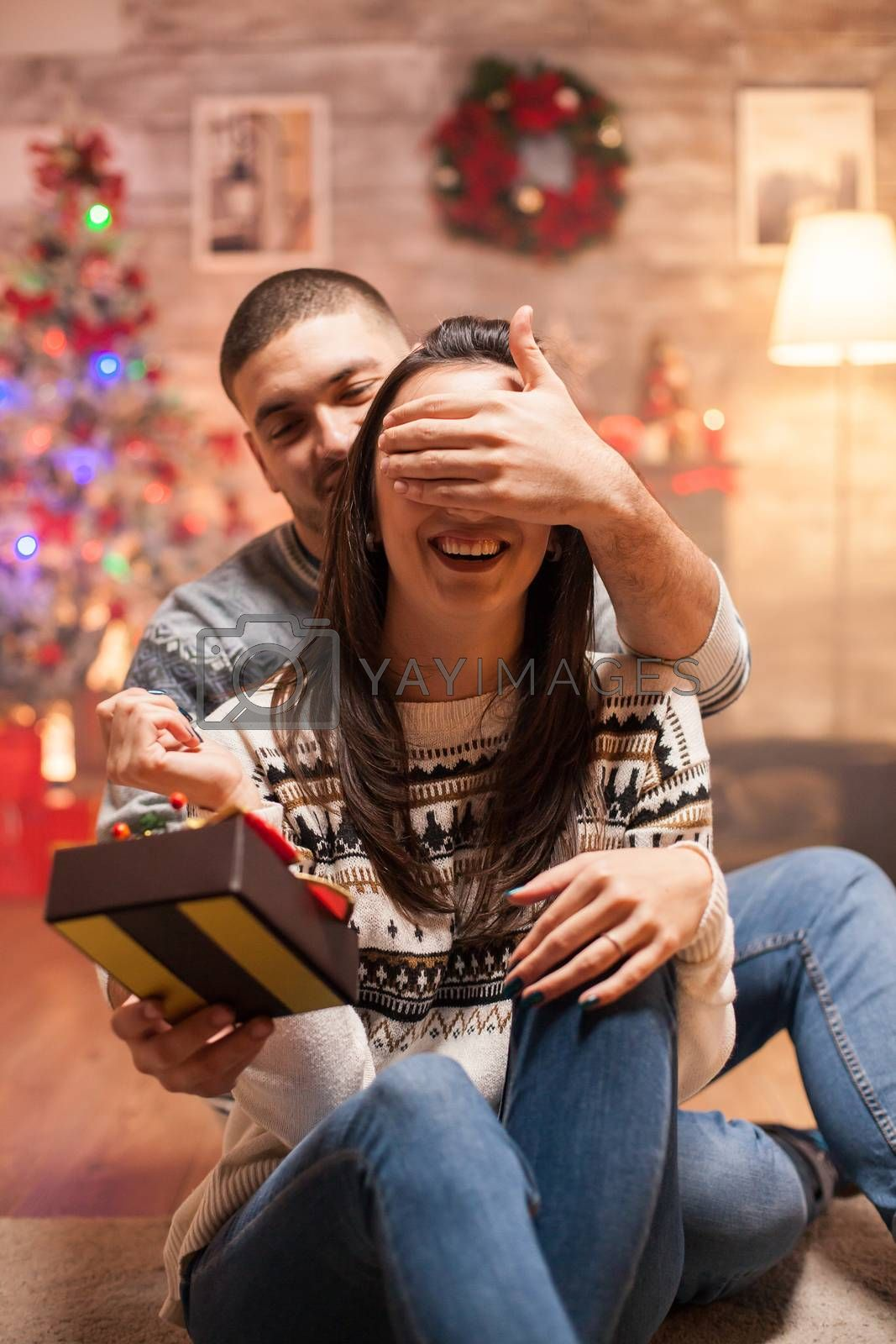 Smiling girlfriend with eyes covered receiving her christmas gift from loving boyfriend.