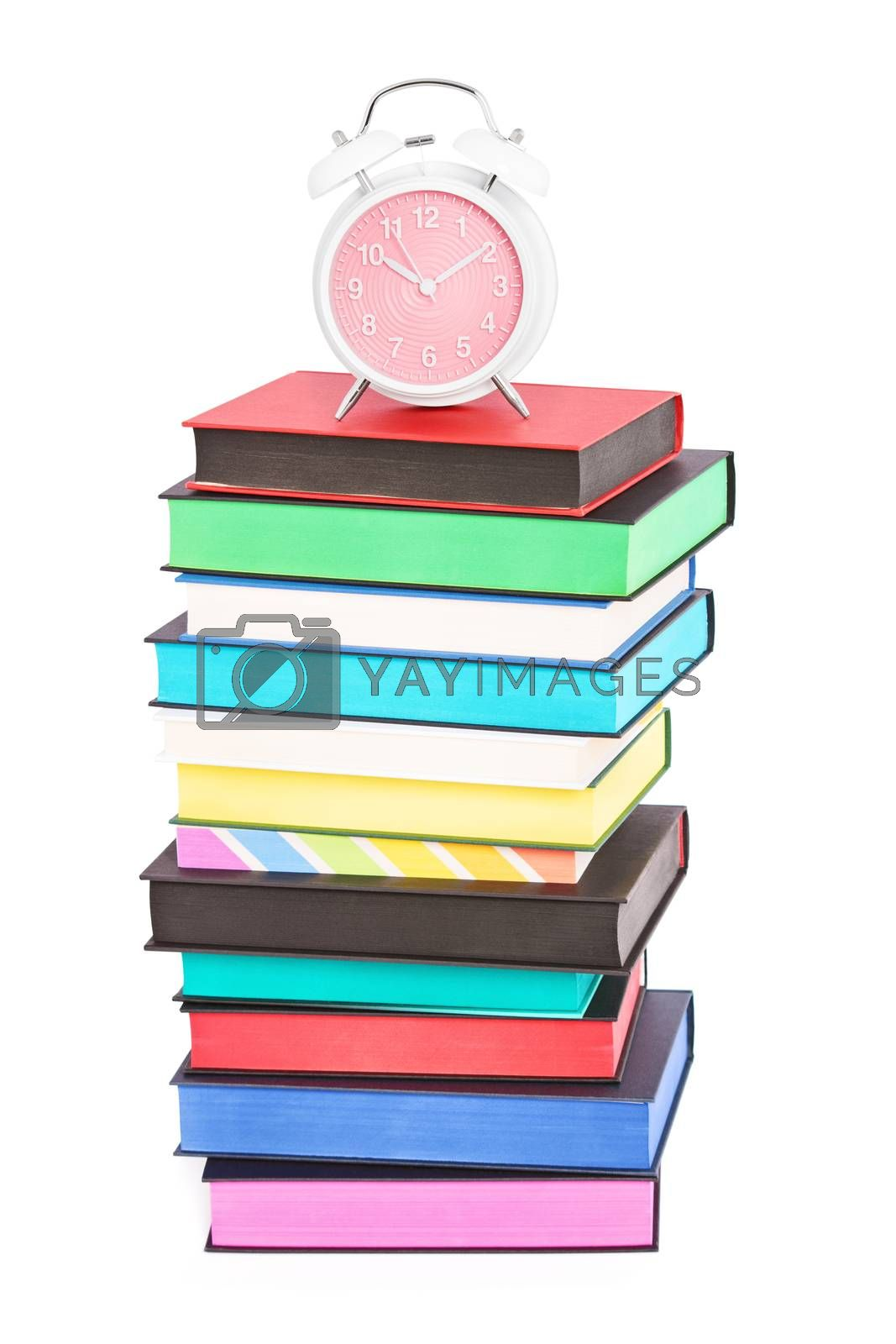 An alarm clock on top of stack of colorful books with different sprayed edges, isolated on white background. Education and time concept.
