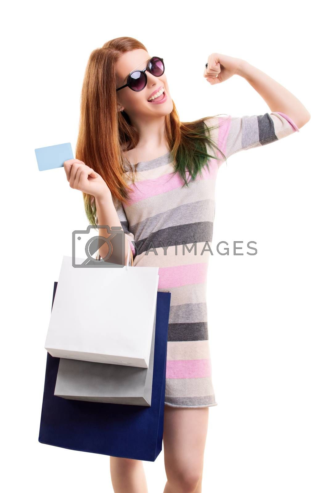 Excited beautiful young girl in a dress with sunglasses, holing shopping bags and a blank card, with raised arm, isolated on white background. Shopping concept, copy space.