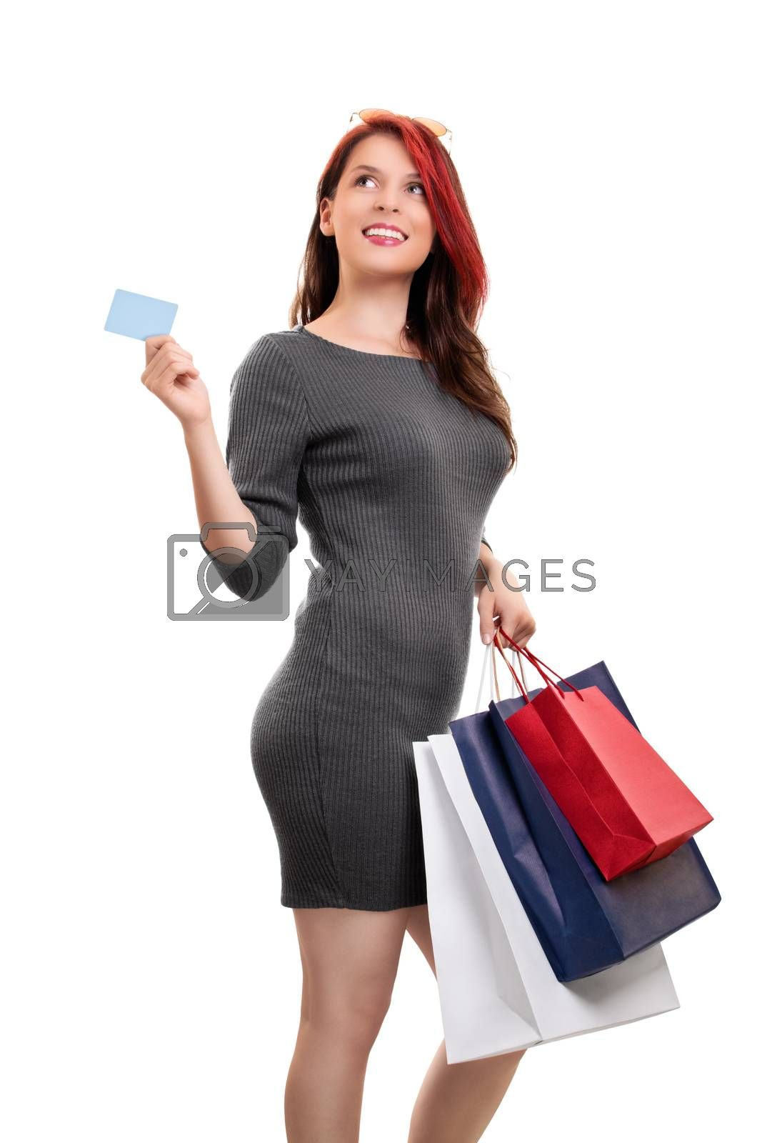 Beautiful young girl in a dress with sunglasses, holing shopping bags and a blank card, isolated on white background. Shopping concept, copy space.