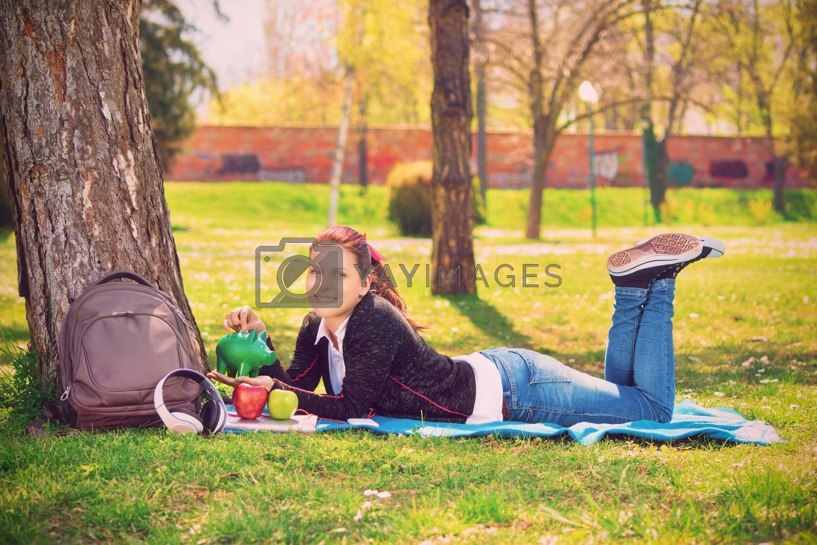 Beautiful smiling young girl lying on the green grass in the park, inserting a coin in a green piggy bank. Savings and money concept. Student saving concept.