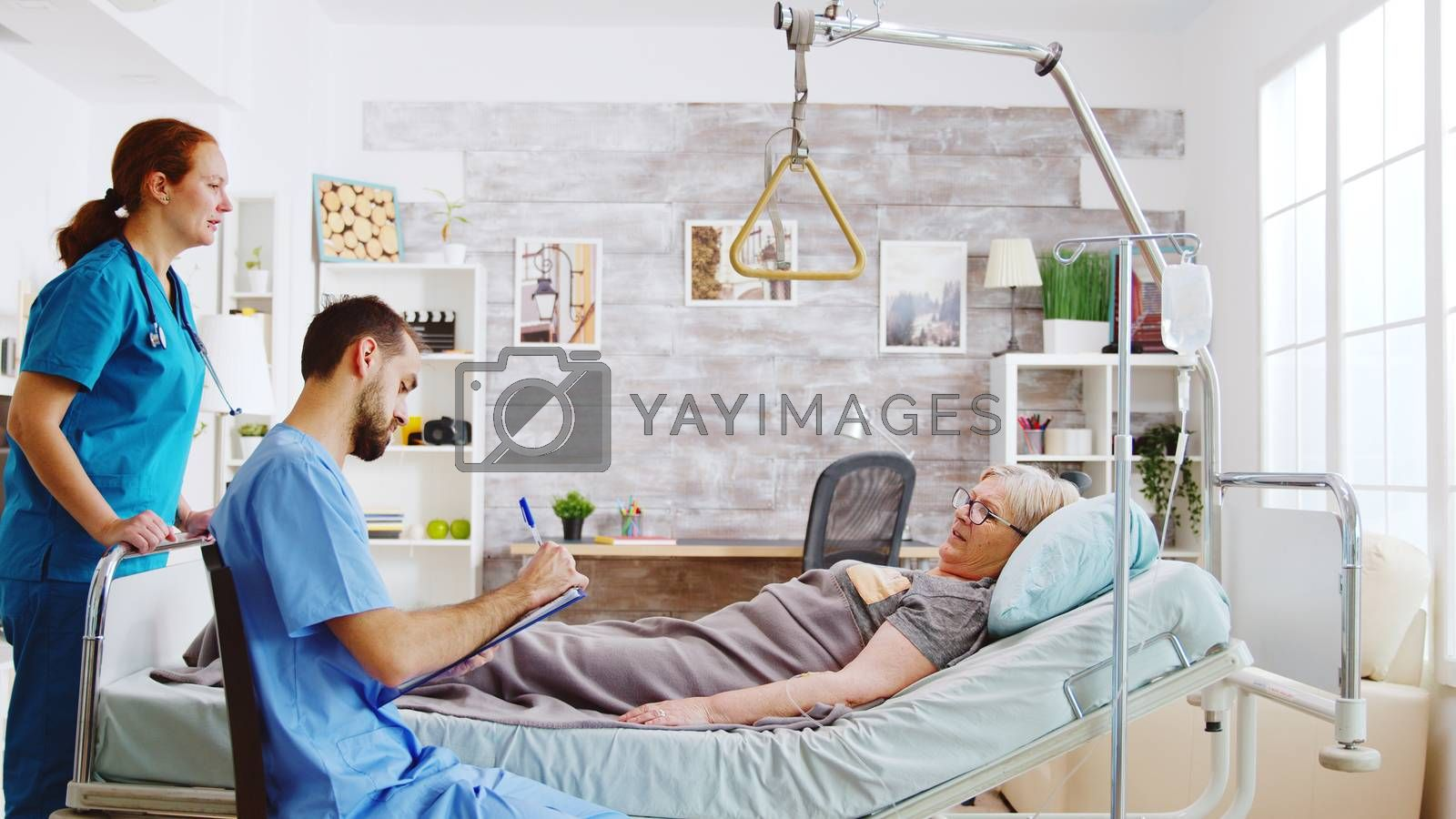 Team of male and female nurses checking an old lady lying in hospital bed in a retirement home