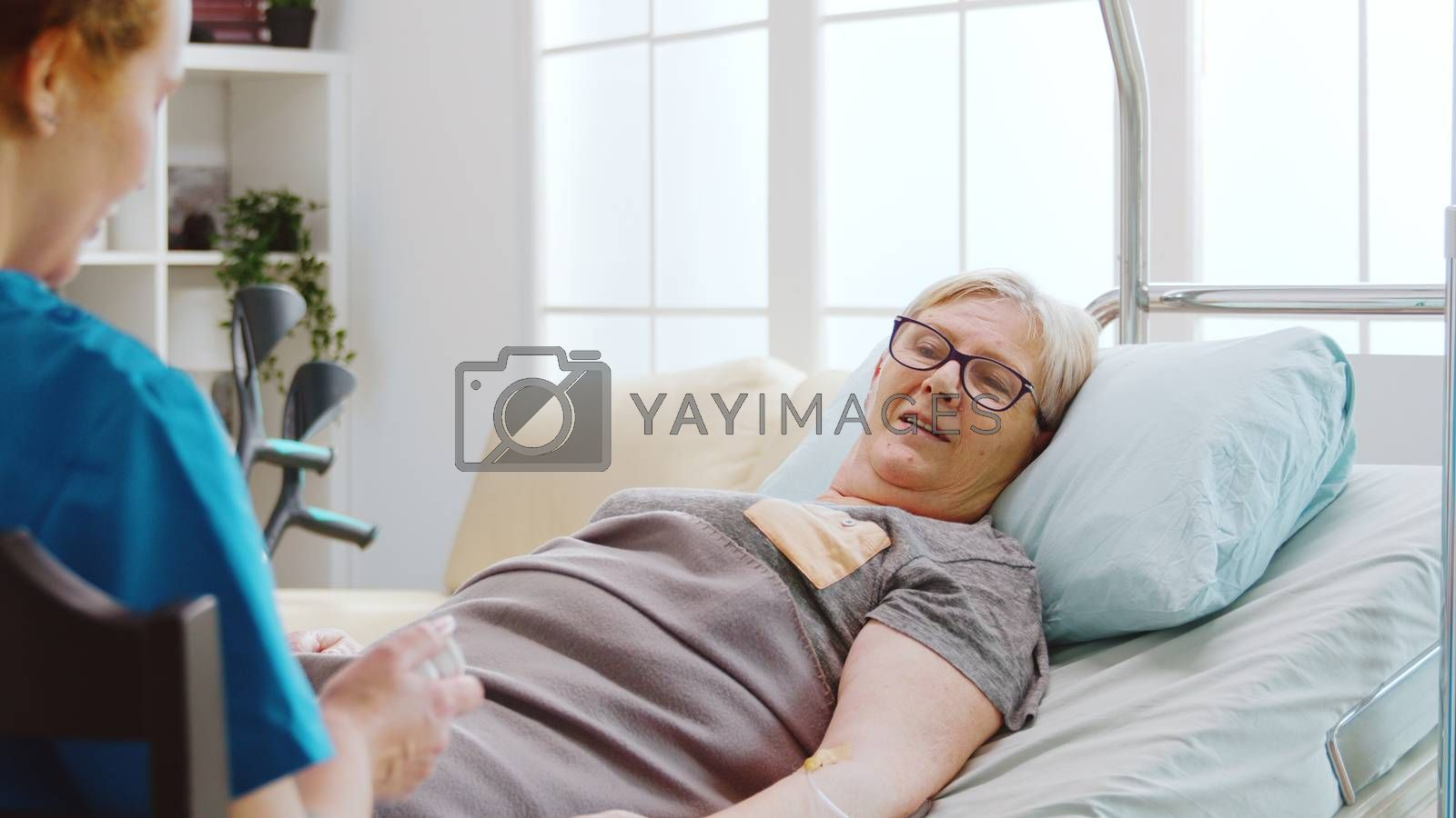 Nurse showing to an old lady what pills dossage to take while she is lying in hospital bed in retirement home
