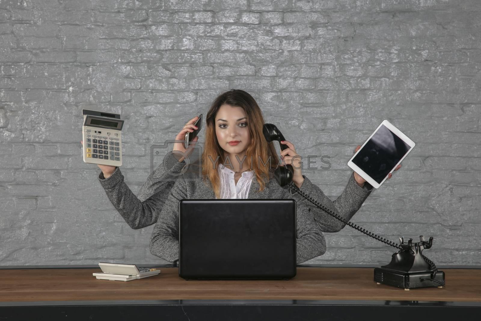 Multitasking business woman sitting at desk