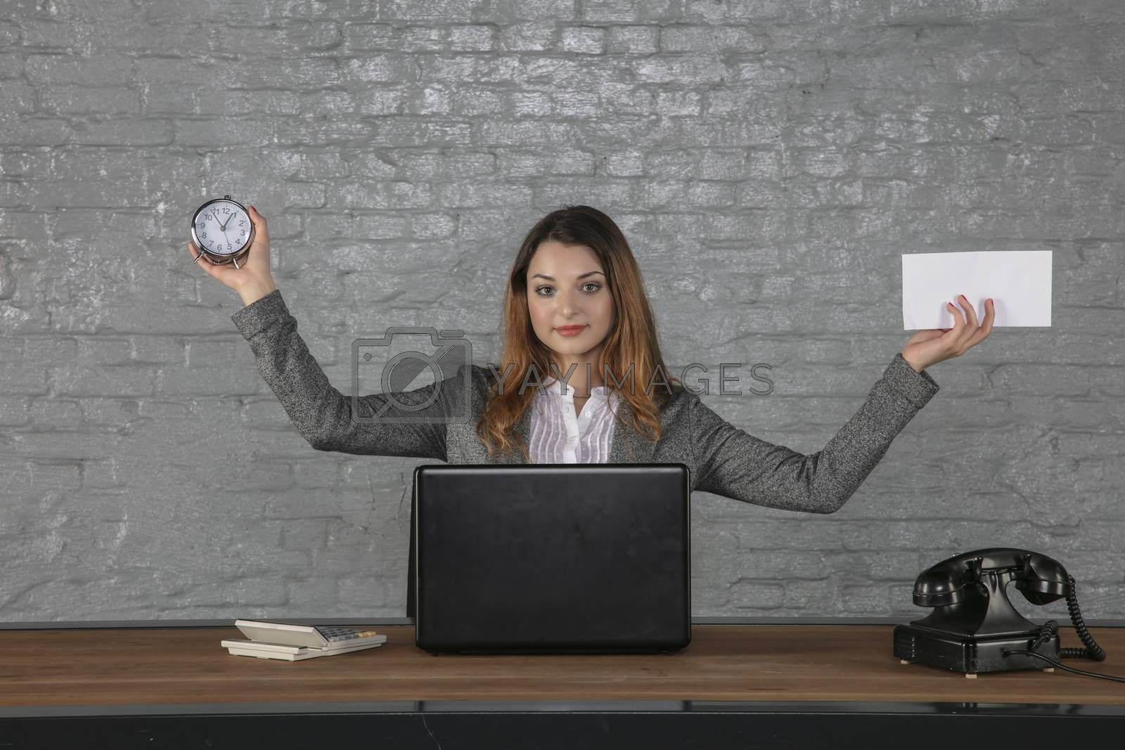 A young business woman holds an envelope and a watch in her hands
