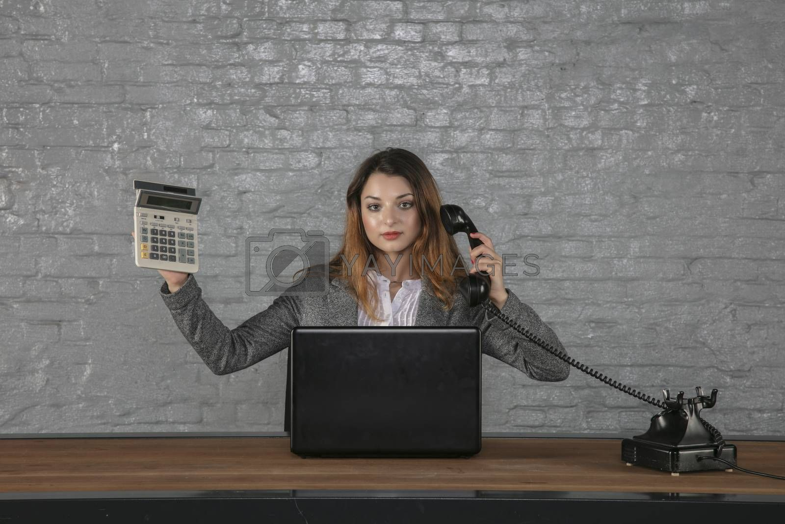 young business woman talking on the phone, holding calculator in her hand