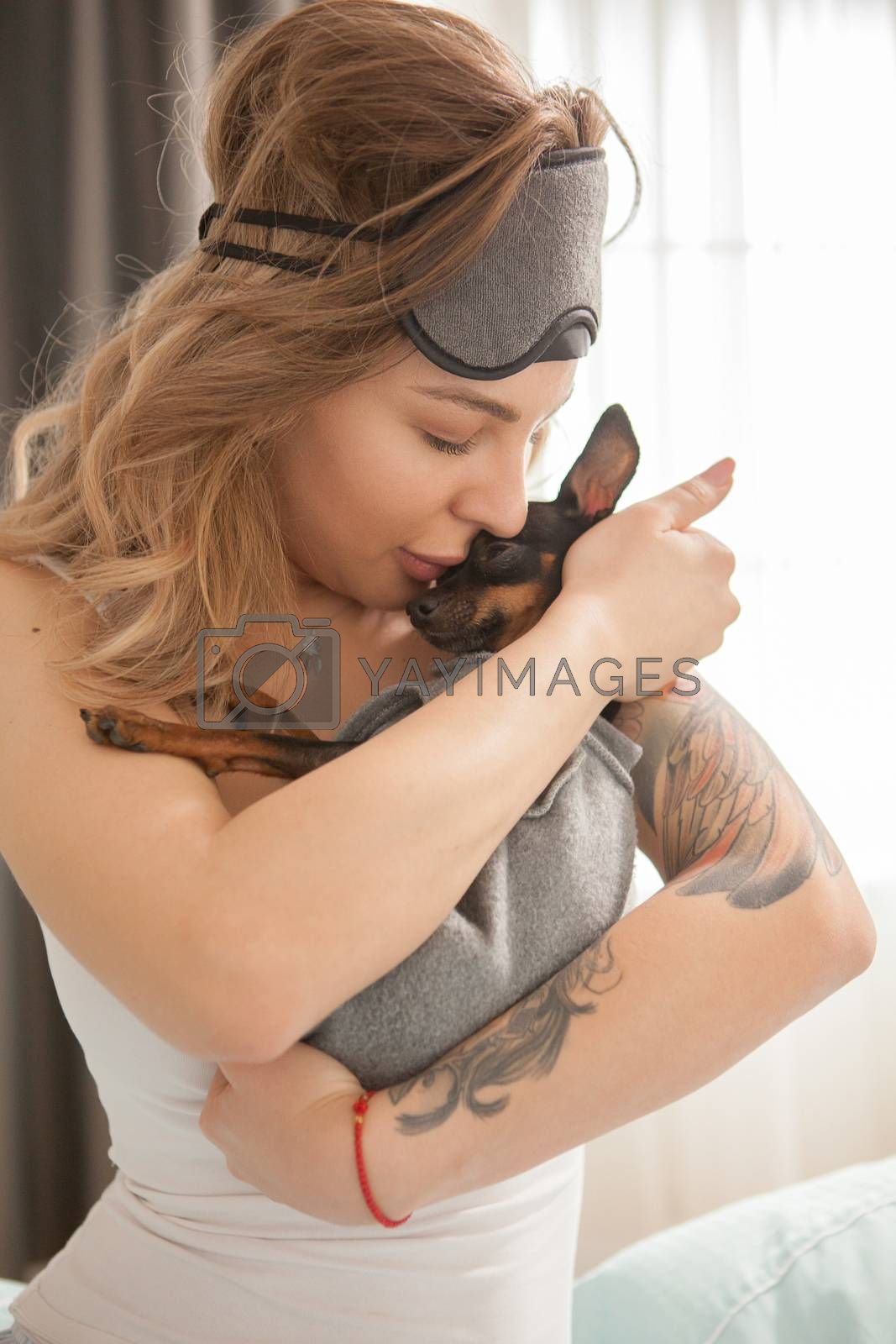 Adorable young woman kissing her little dog in the morning after waking up.