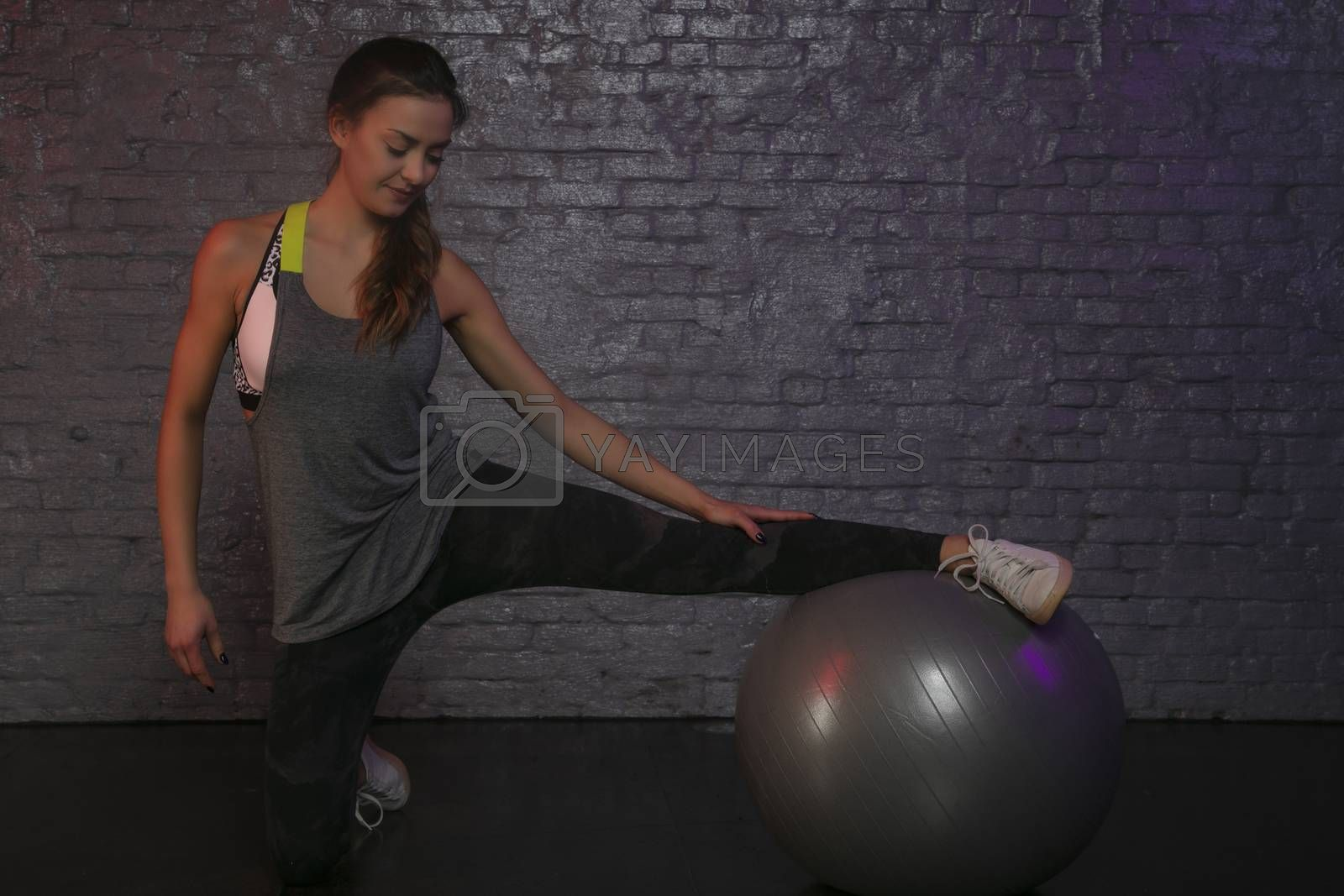 beautiful athletic girl practicing with a ball at the gym, pretty silhouette