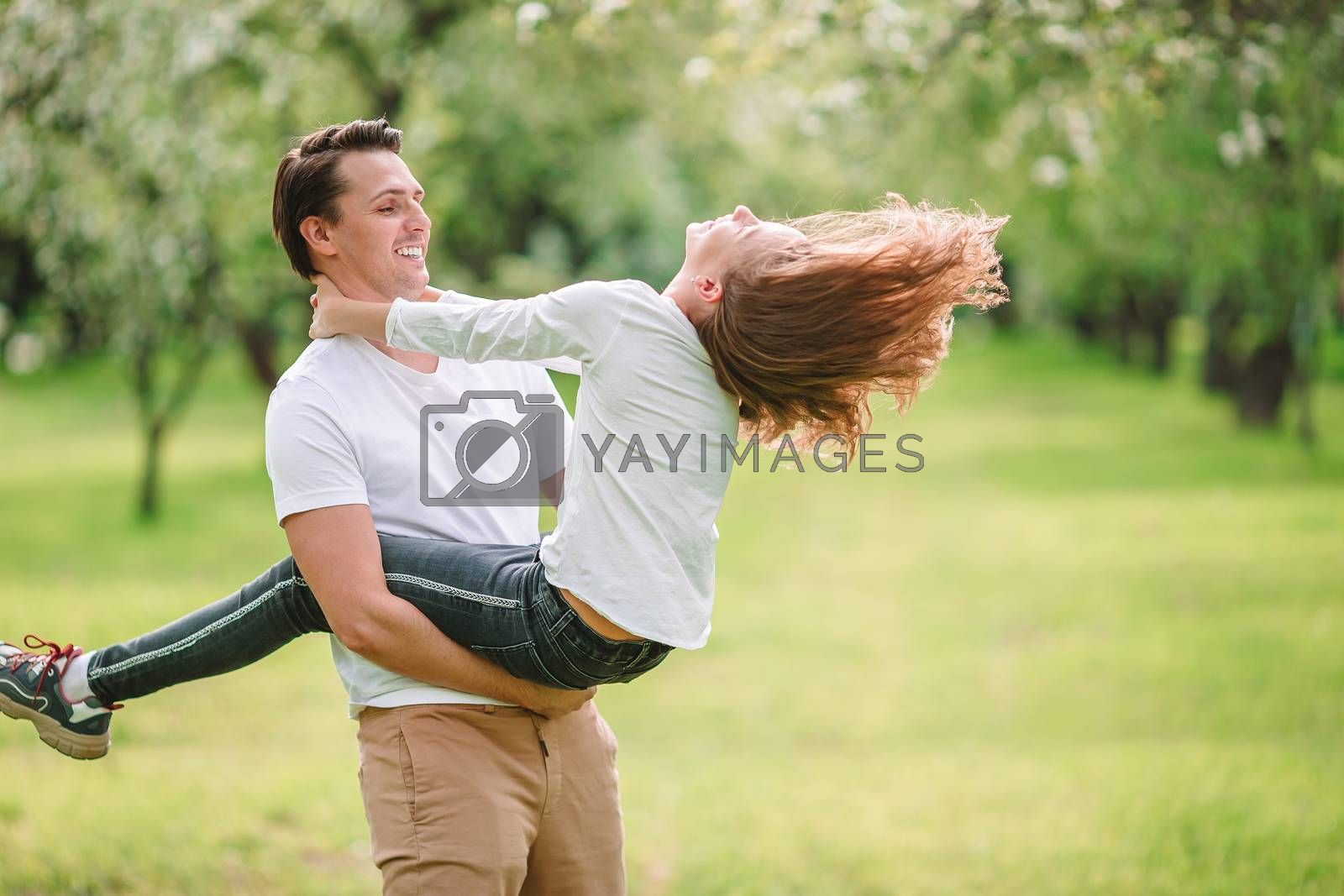 Family of dad and little girl having fun outdoors in the park