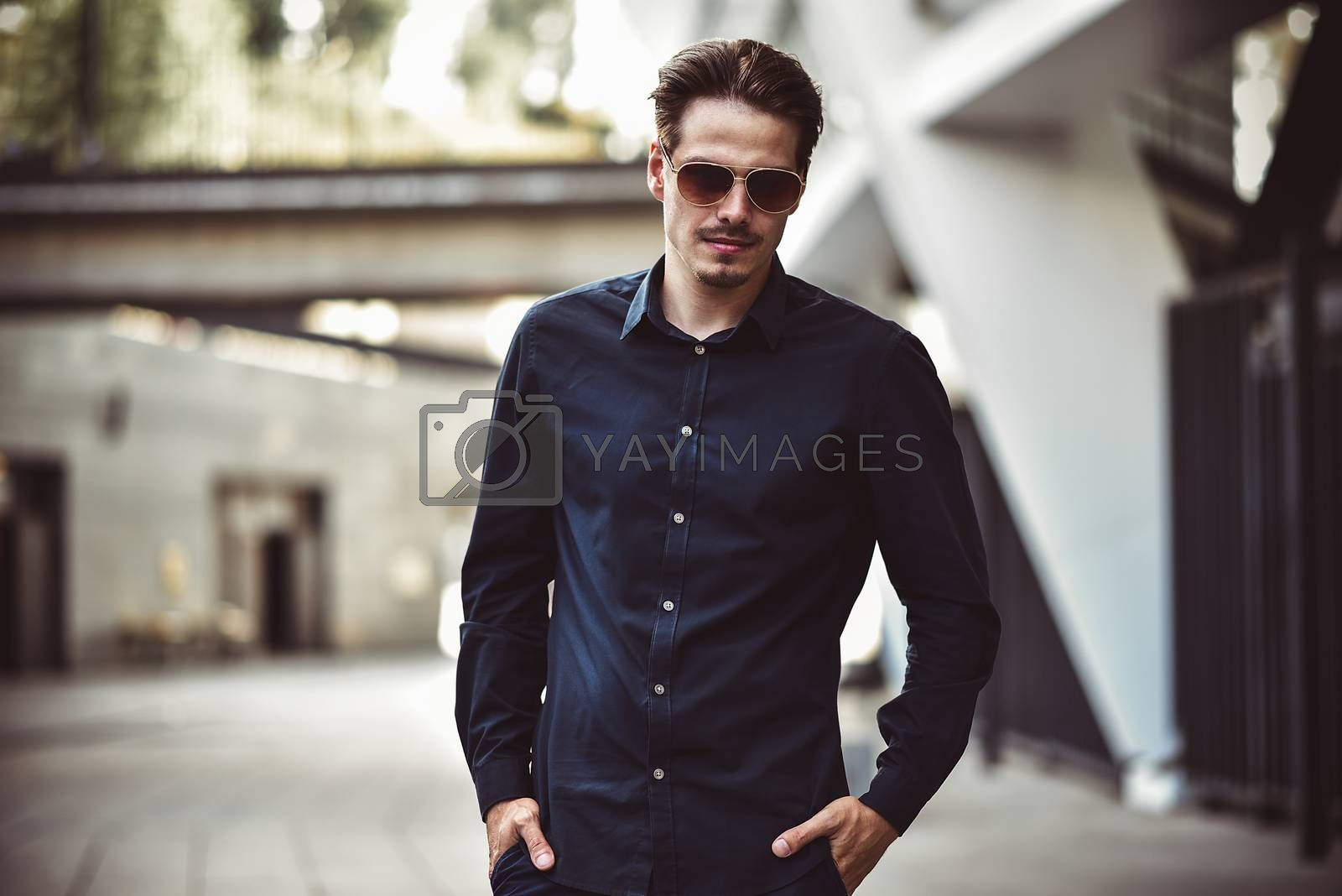 Young stylish and confident happy handsome businessman model in shirt lifestyle in the street in sunglasses