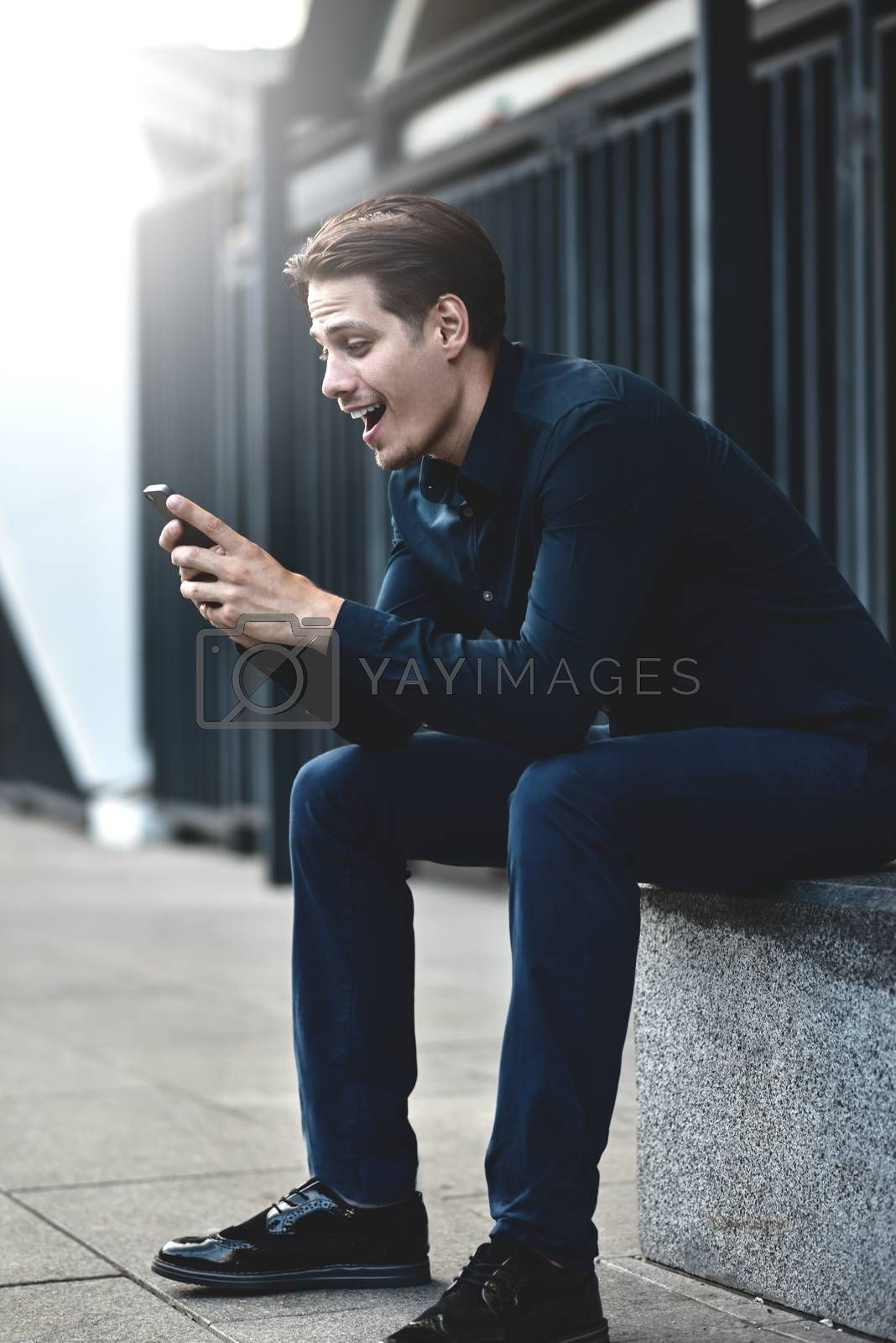 Successful caucasian businessman with smartphone at street in the city.
