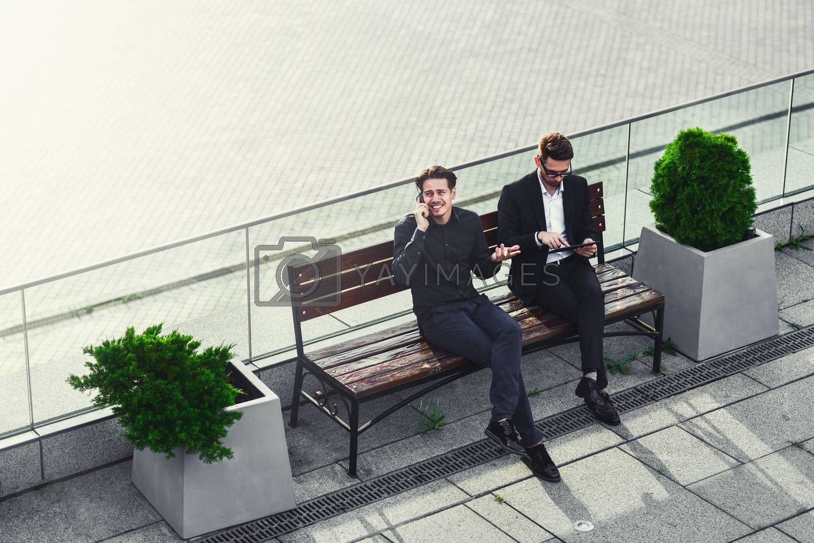 Two Businessman's have a conversation on street bench busy by phone and tablet.